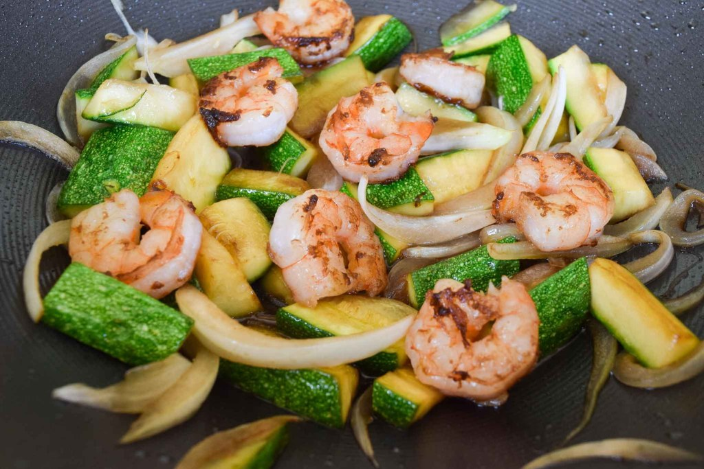 wok filled with cooked shrimp, onions and zucchini slices