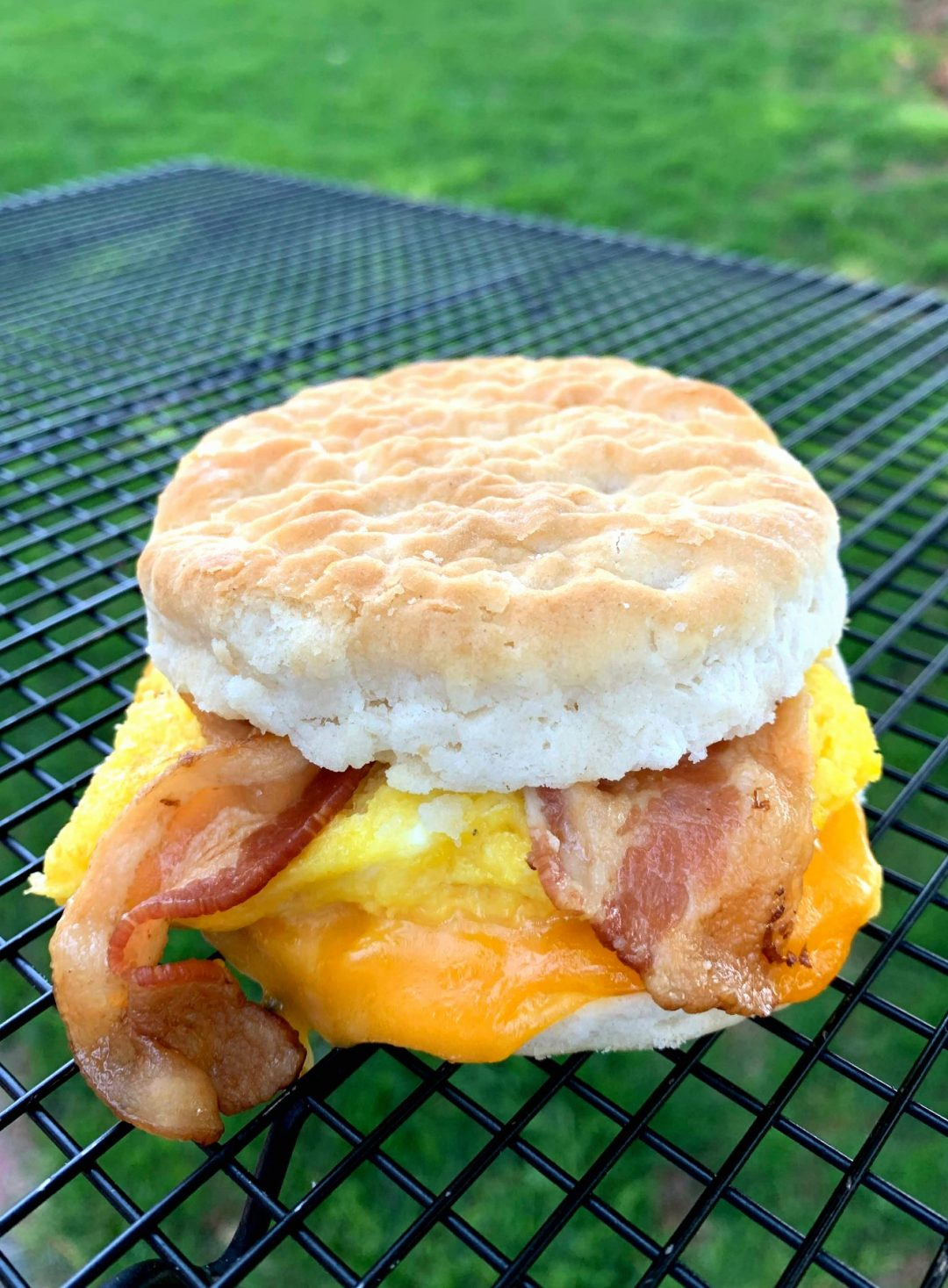 a cooling rack with a bacon, egg and cheese biscuit sandwich on top of it