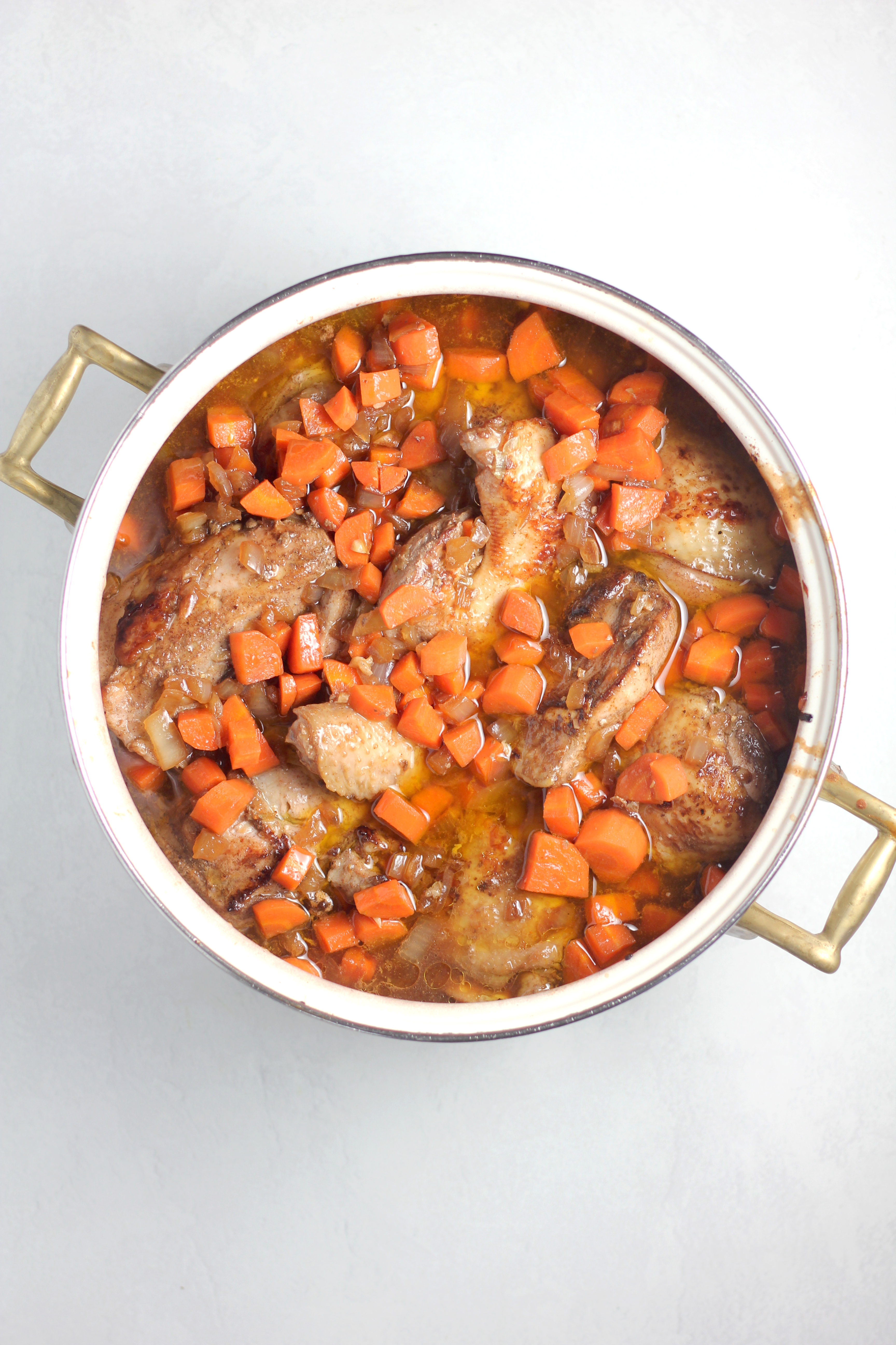 a dutch oven filled with Jamaican Brown Stew Chicken