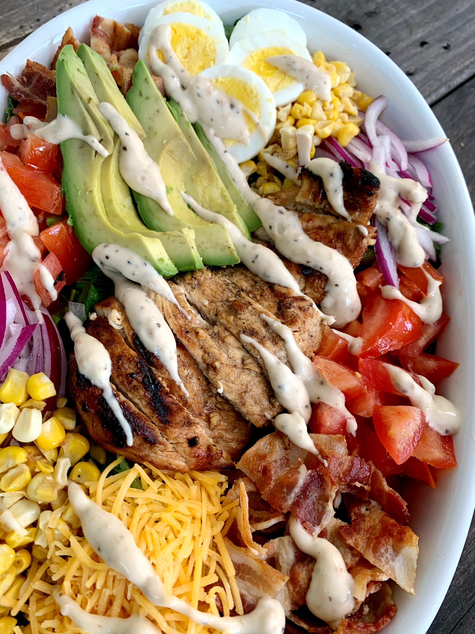 up close shot of Cobb Salad with dressing drizzled over it