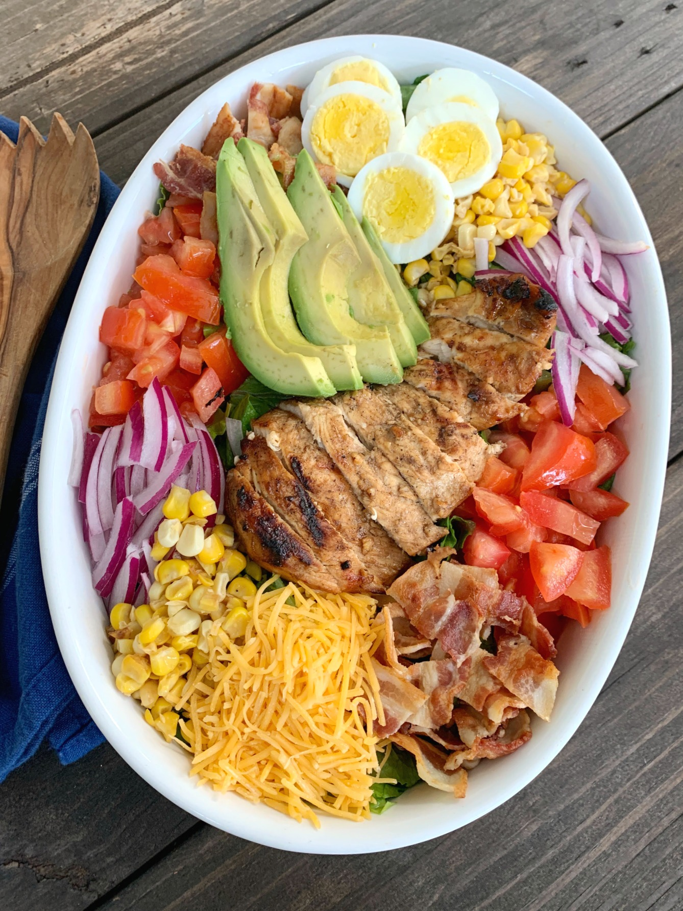 a white oval dish packed with a grilled chicken cobb salad with wooden salad utensils beside it