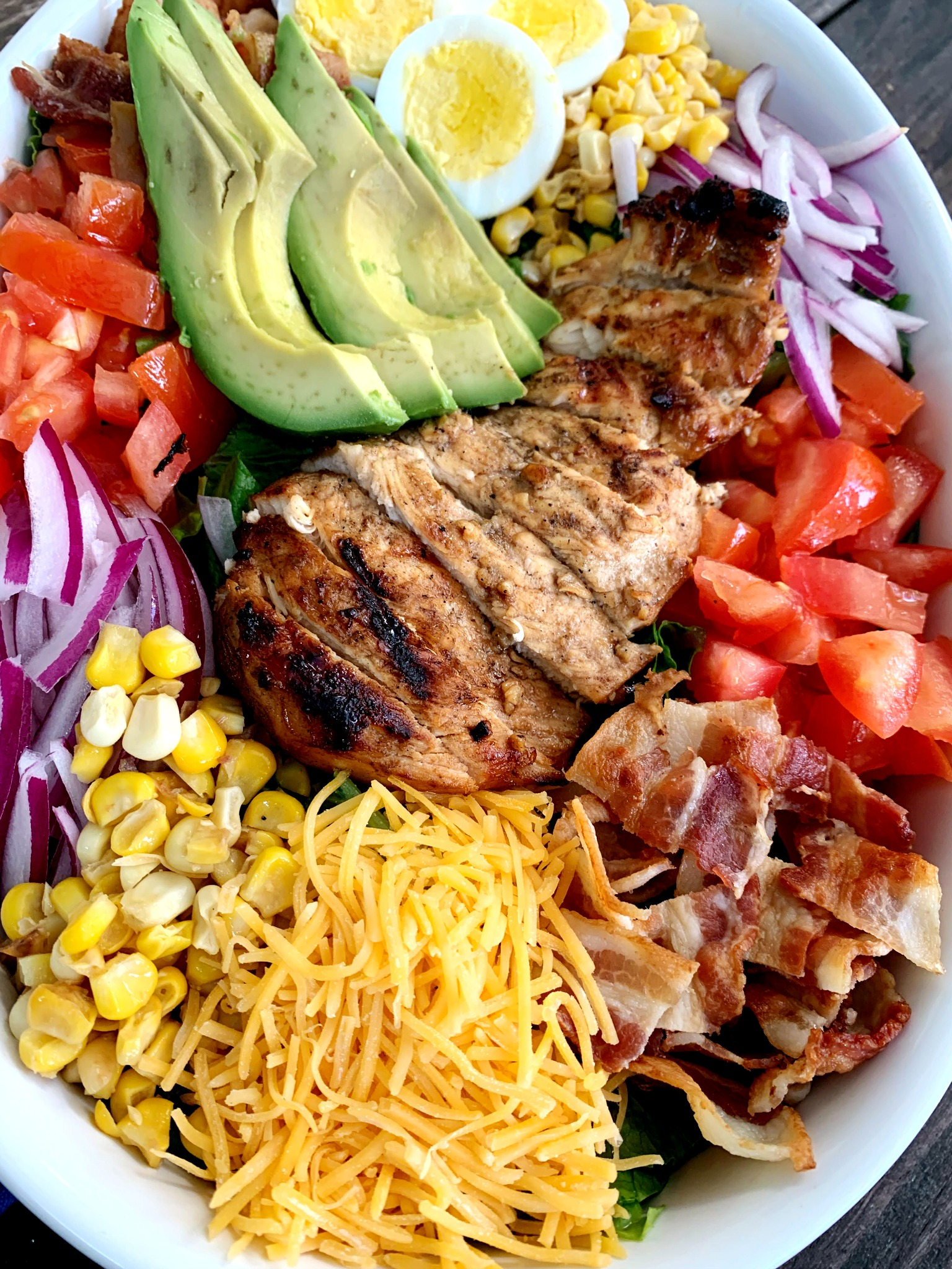 up close shot of cobb salad with sliced marinated chicken on top