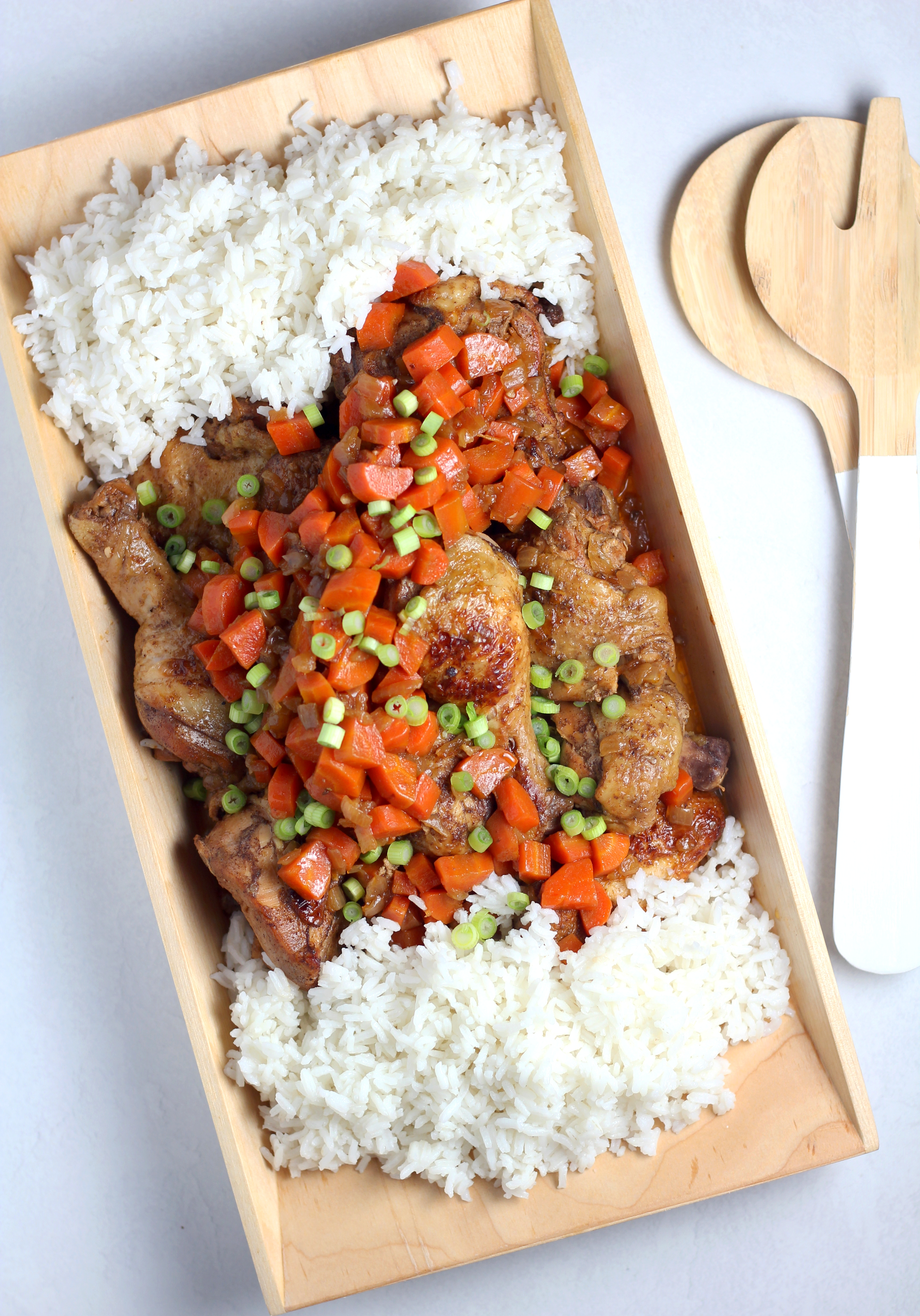 a rectangle dish with white rice on either end and Jamaican Brown Stew Chicken in the middle