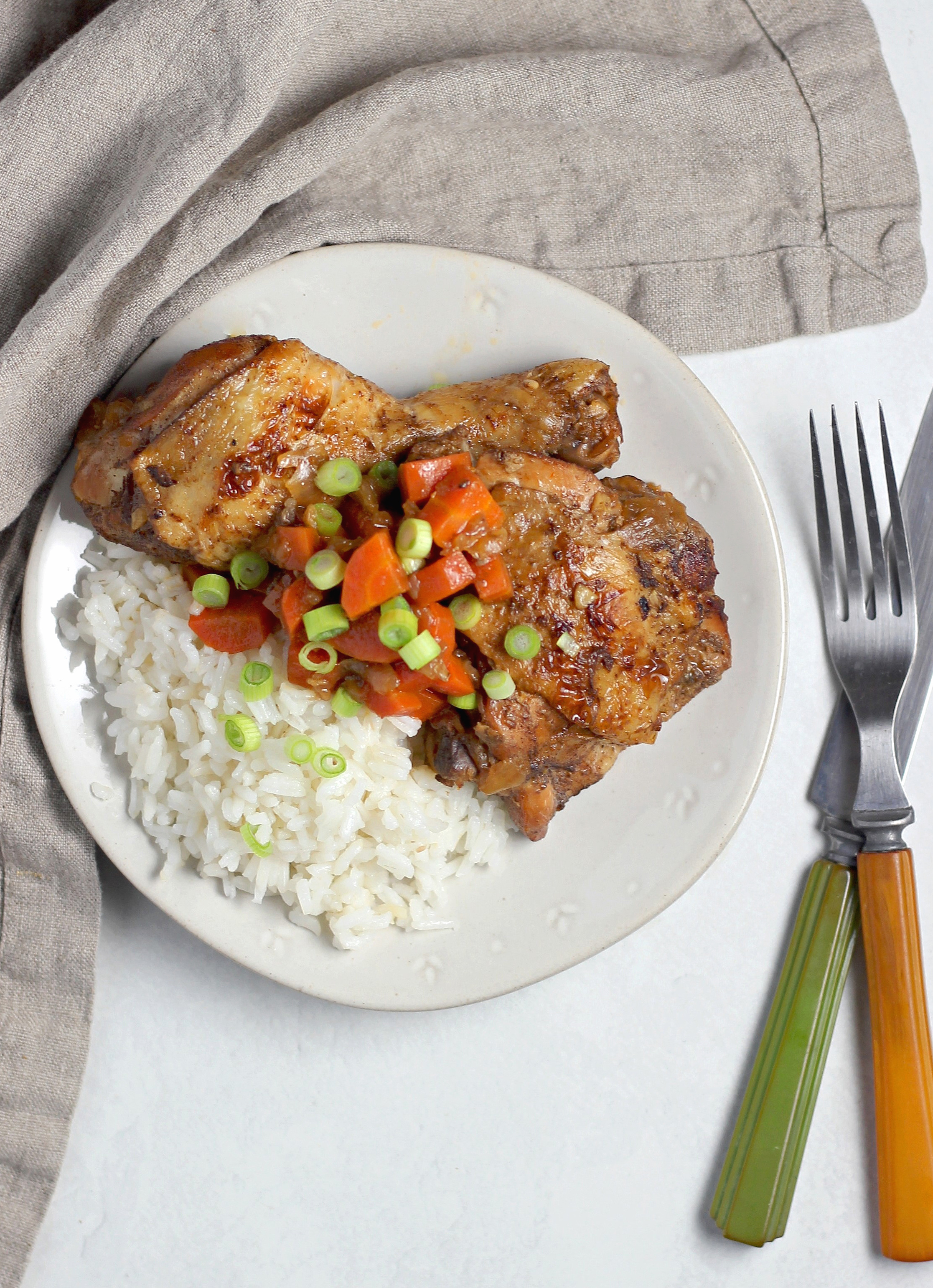 a white plate with white rice and Jamaican brown stew chicken with a knife and fork off to the side