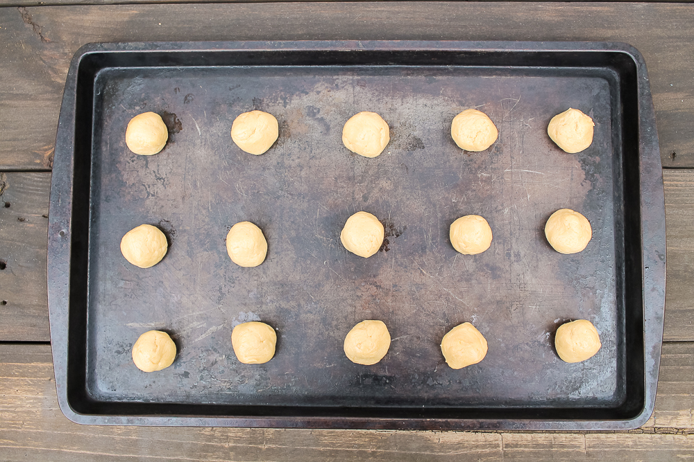 a cookie sheet with 12 balls of peanut butter cookie dough