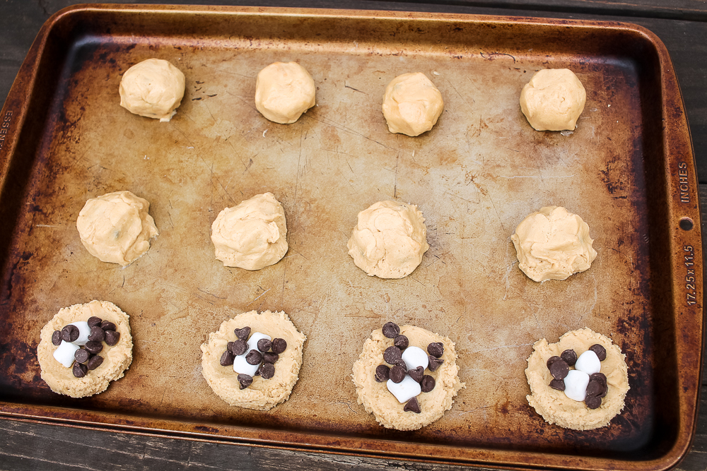 a cookie sheet with peanut butter cookie dough balls and 4 of them have mini marshmallows and chocolate chips in the center