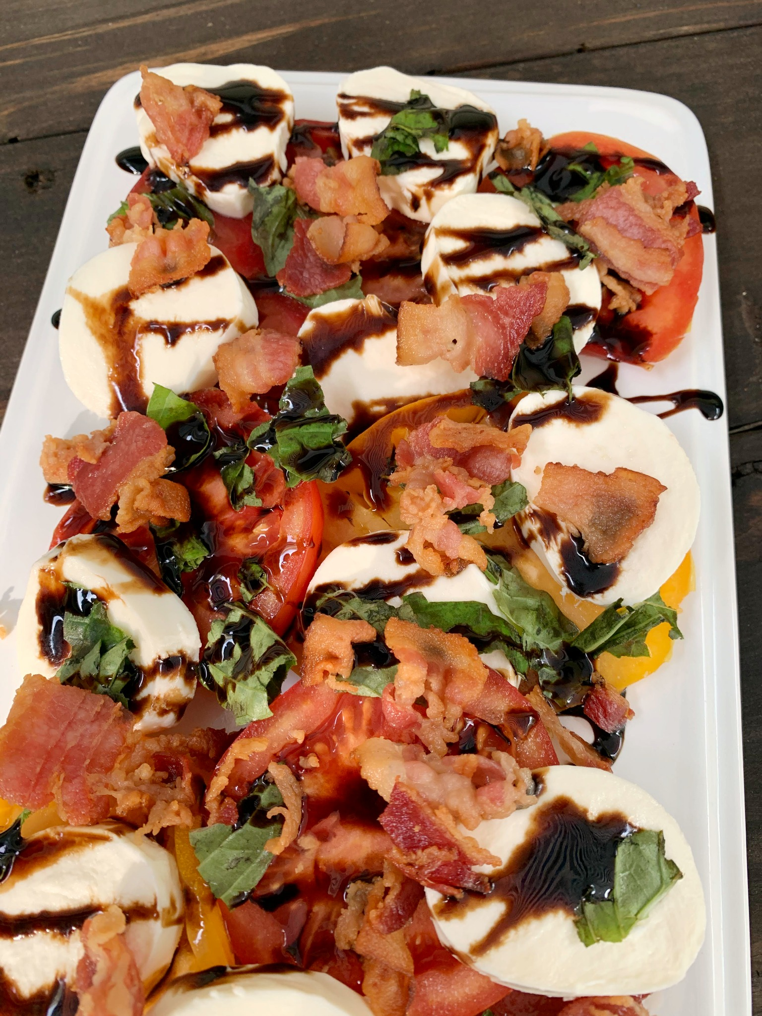 up close shot of caprese salad with crumbled bacon on a white dish