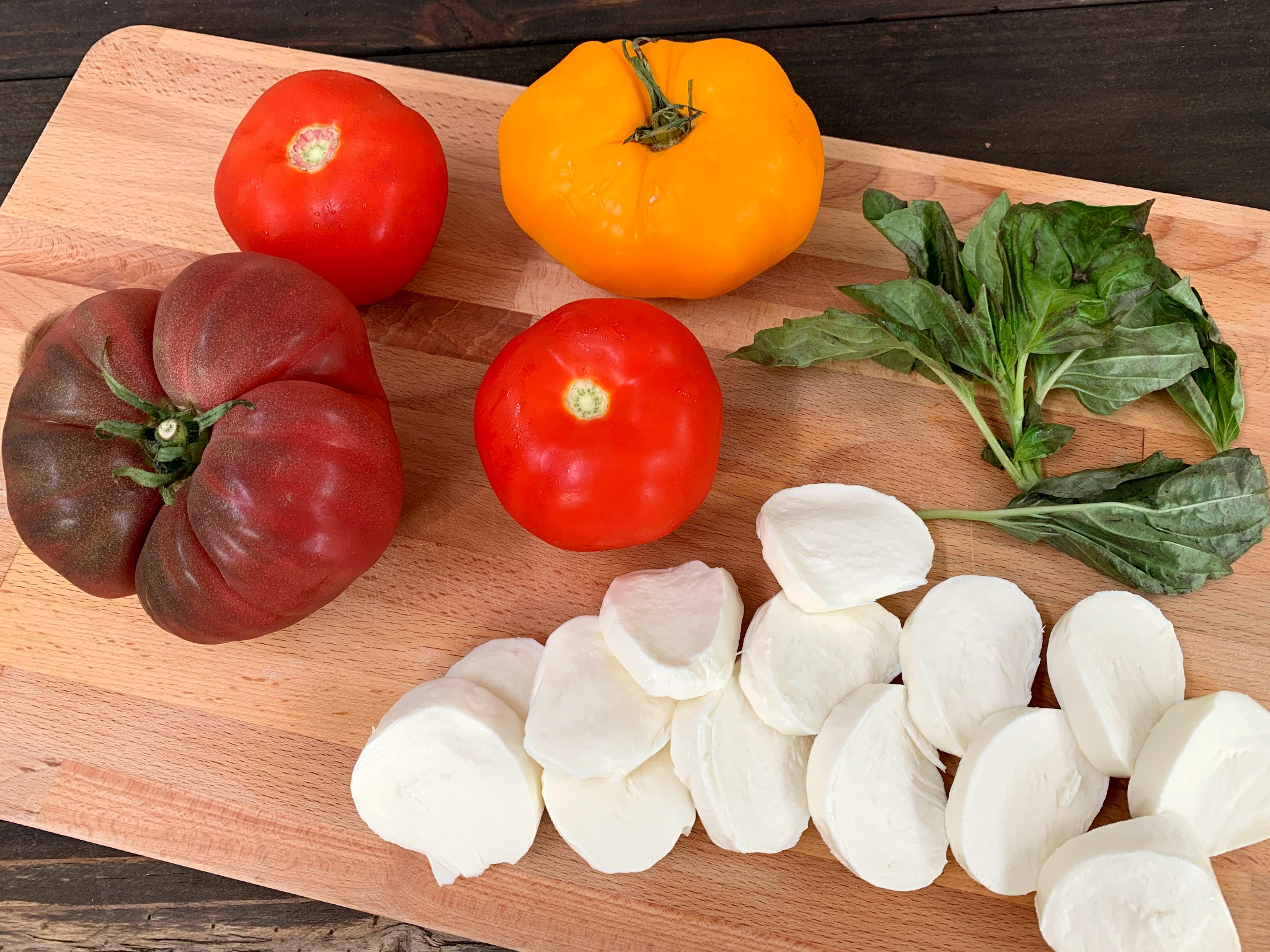 wooden cutting board with whole tomatoes, sliced mozzarella and basil leaves