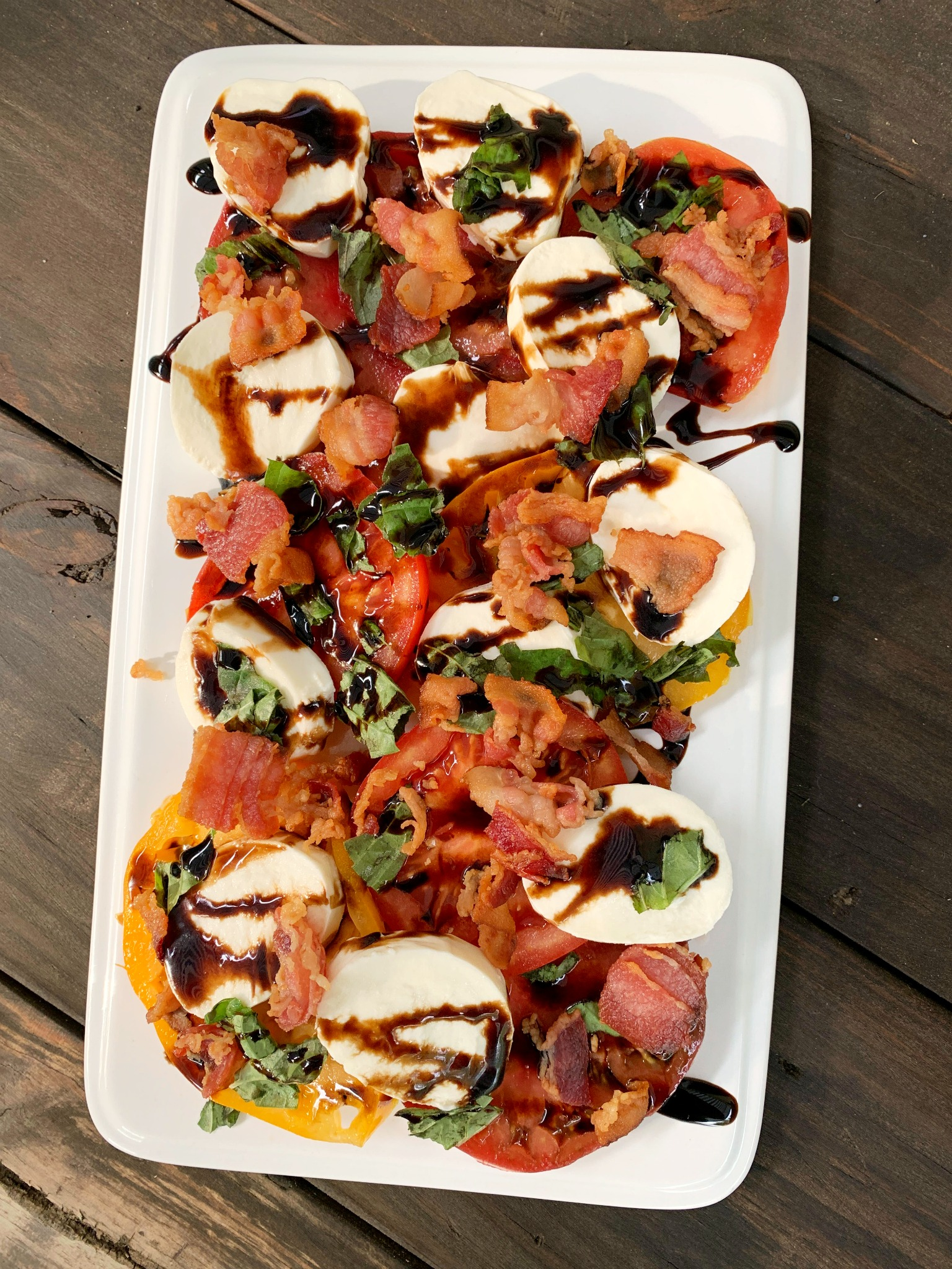 white rectangle tray with caprese salad with bacon
