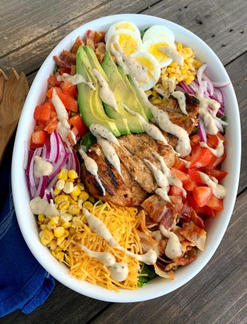 white oval dish filled with cobb salad and drizzled with dressing