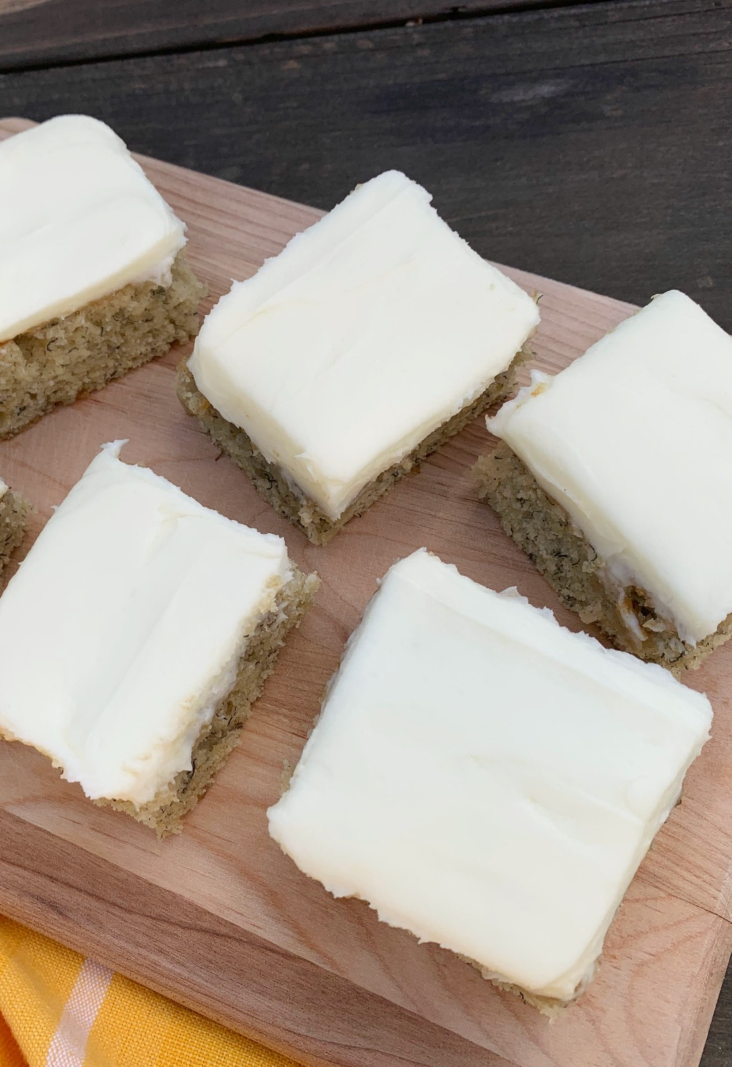 a wooden cutting board with slices of banana cake with cream cheese frosting
