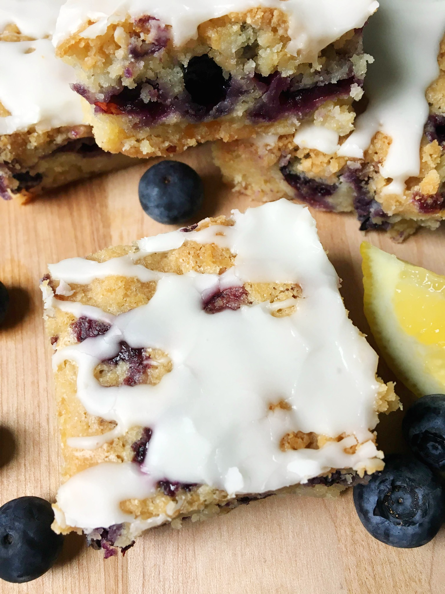 overhead slices of lemon blueberry coffee cake on a cutting board with blueberries scattered around