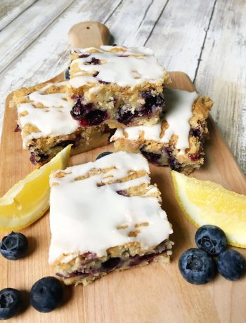 slices of lemon blueberry coffee cake on a cutting board with blueberries scattered around
