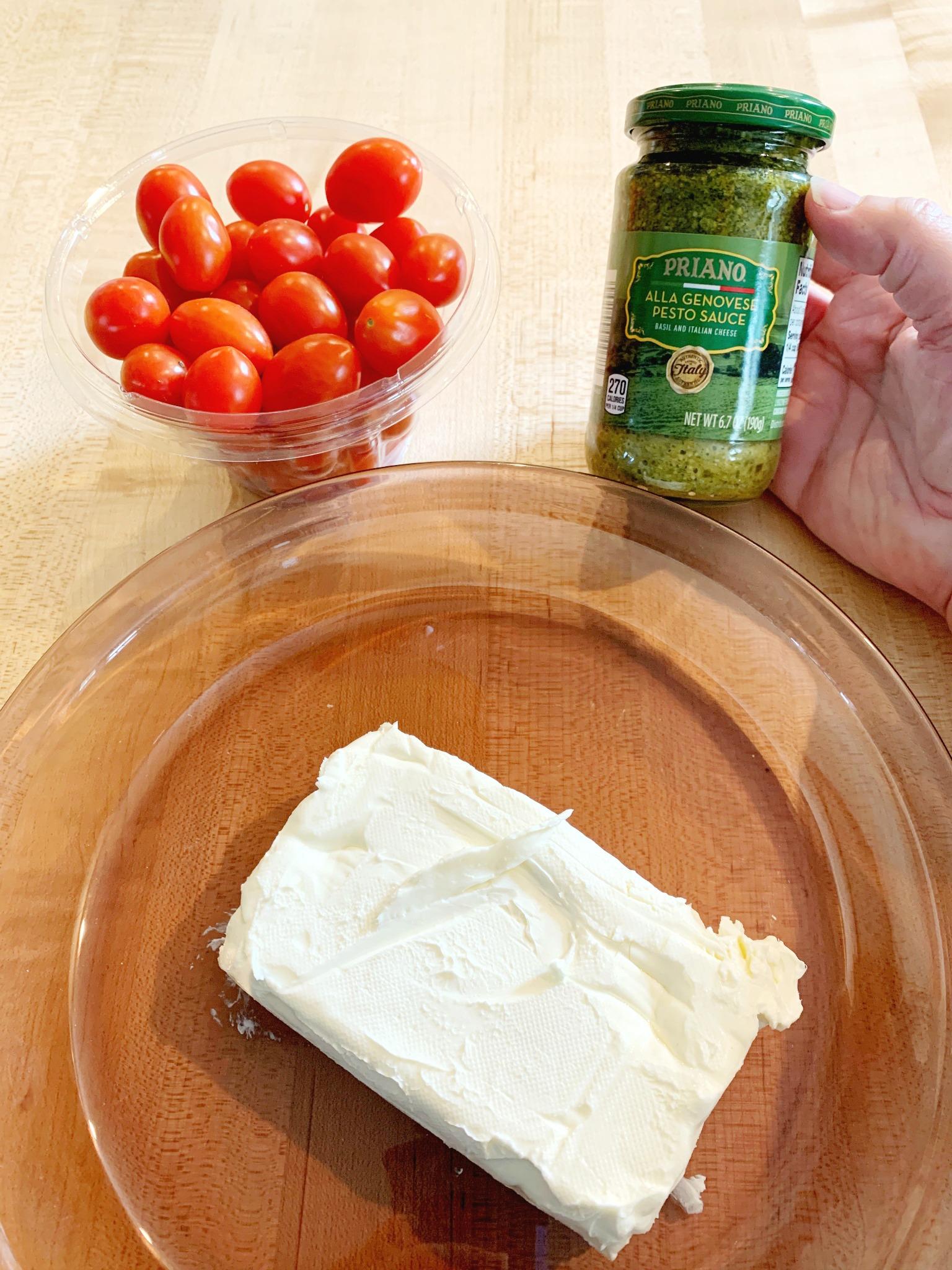 pie dish, block of cream cheese, pint of cherry tomatoes and jar of pesto