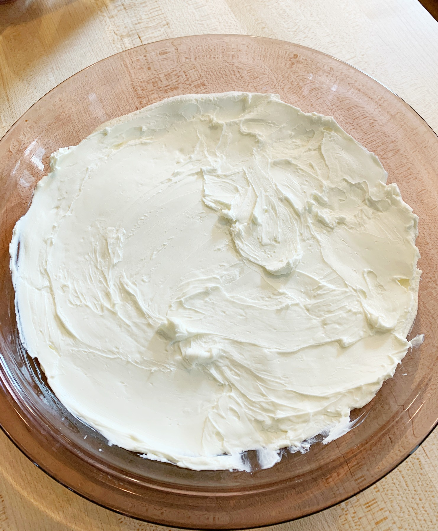 pie dish with cream cheese spread on the bottom