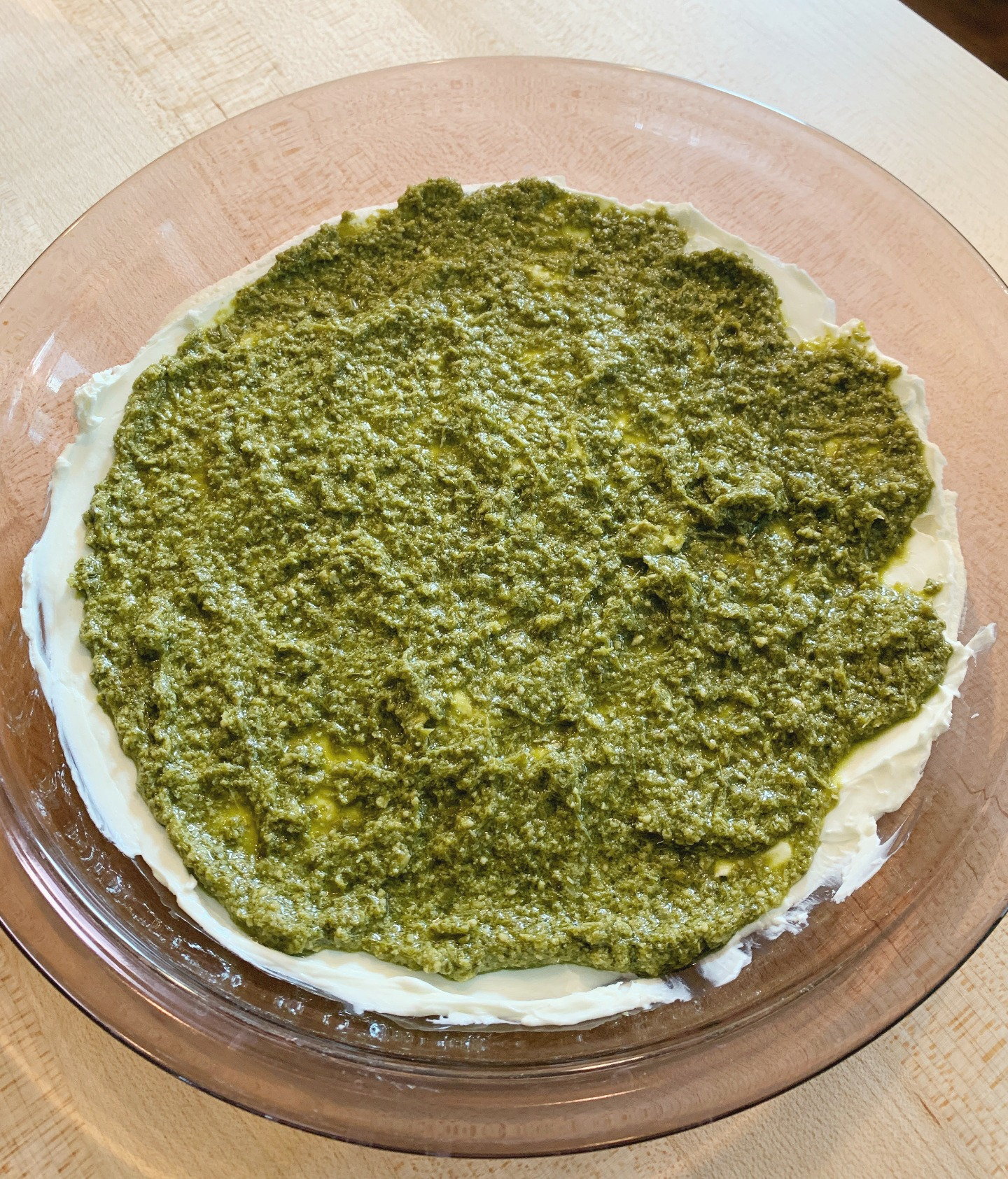 pie dish with cream cheese spread on the bottom and pesto on top