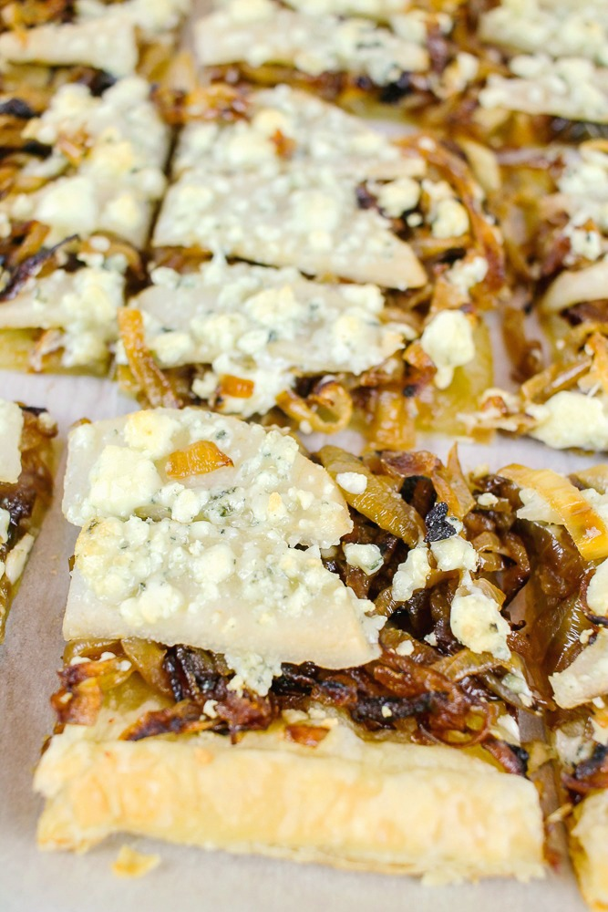 up close shot of a slice of puff pastry tart with caramelized onions, pears and gorgonzola
