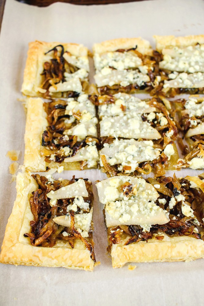 a sheet of puff pastry topped with pears, gorgonzola and caramelized onions that is cut into squares