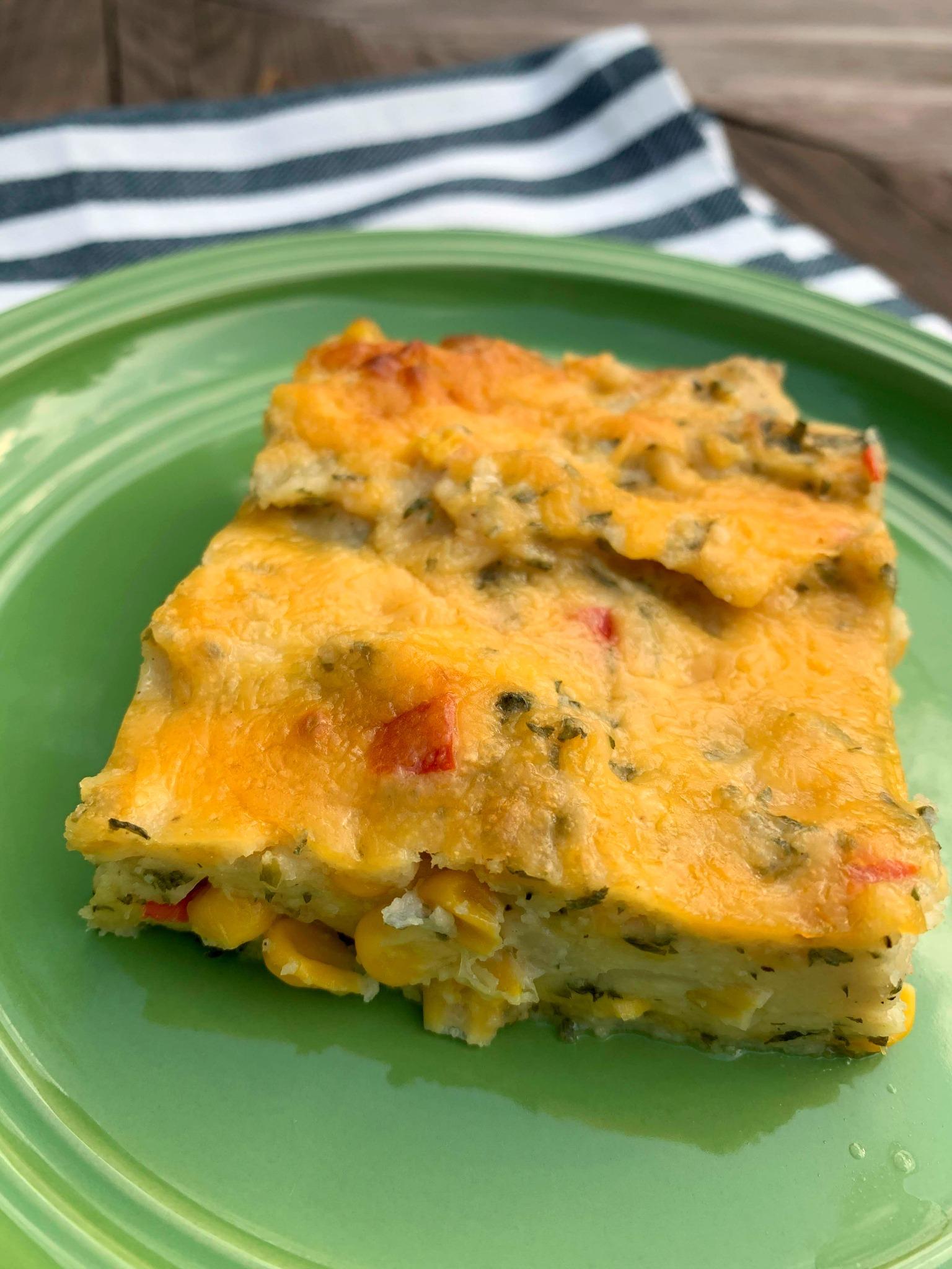 a slice of corn pie casserole on a green plate