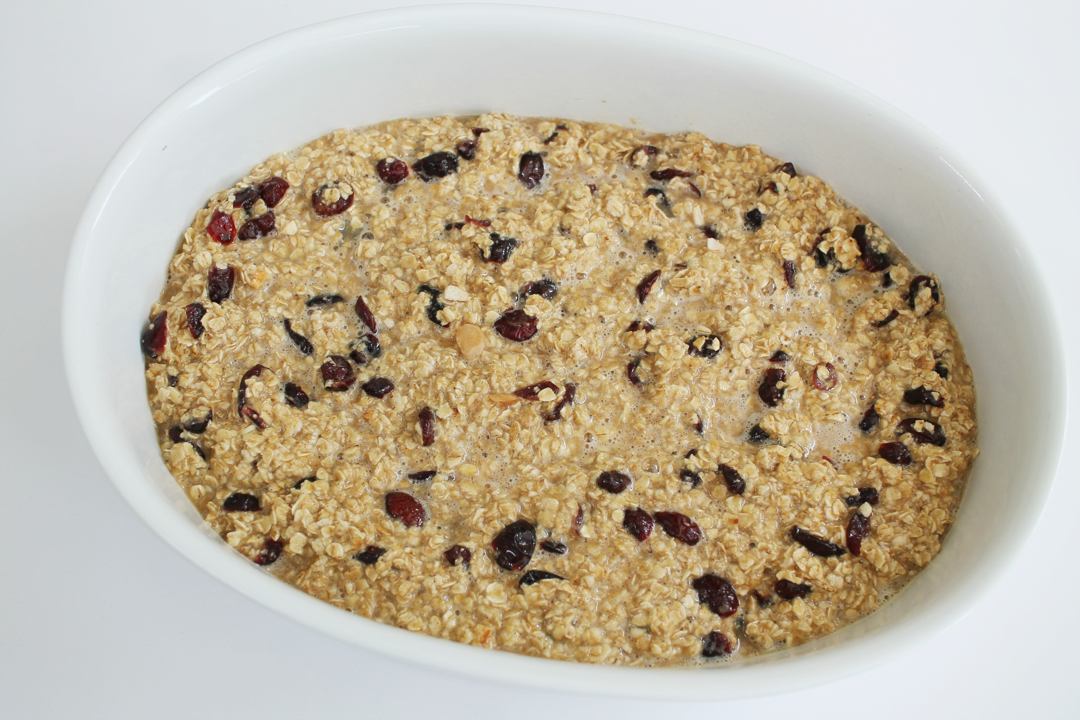 a white oval casserole dish with cranberry almond baked oatmeal before it's cooked