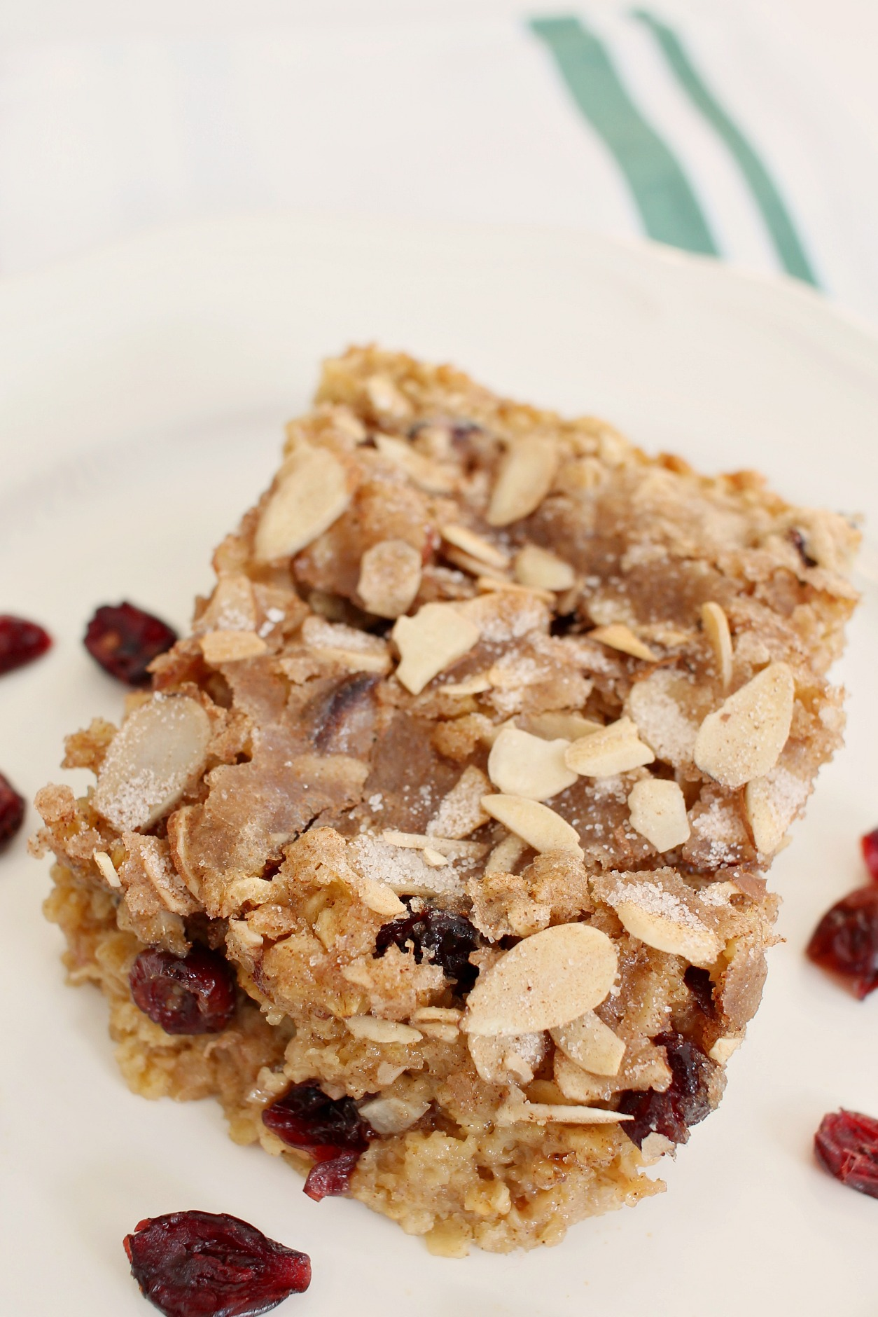a slice of cranberry almond baked oatmeal on a white plate