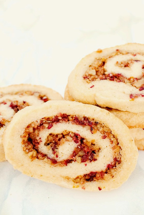 up close shot of a cranberry walnut pinwheel cookie with more stacked behind it