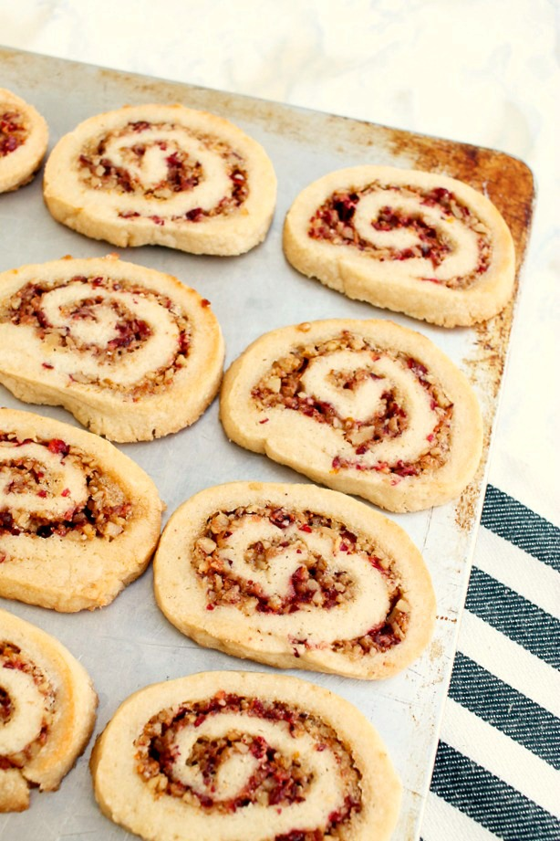 cranberry pinwheel cookies lined up on a cookie sheet