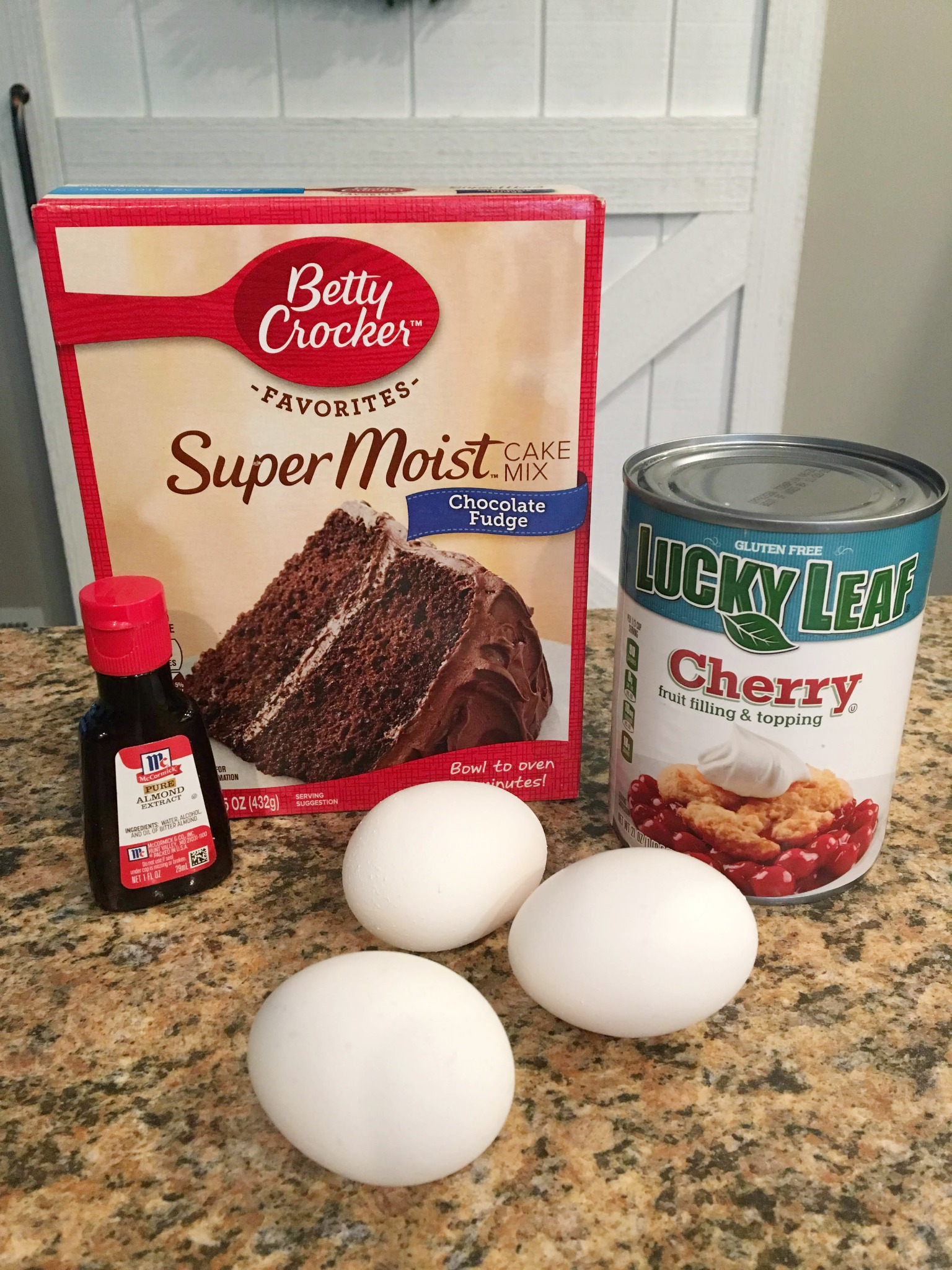 ingredients for chocolate cherry cake on the counter: a box of cake mix, a can of cherry pie filling, 3 eggs and a bottle of almond extract