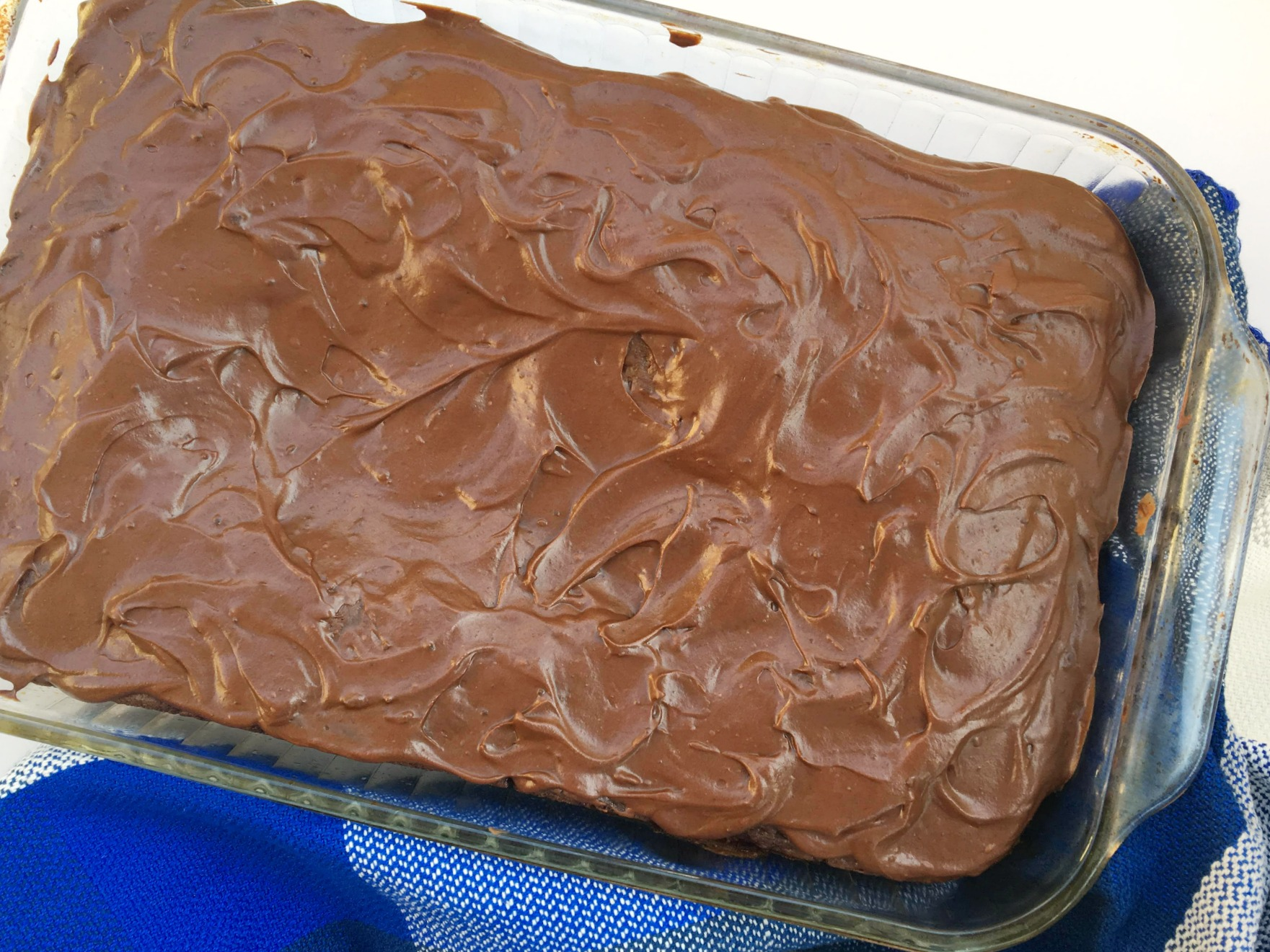 glass 13x9 pan with chocolate cake covered in chocolate frosting with a blue tea towel underneath