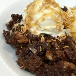 white bowl with German chocolate bread pudding topped with vanilla ice cream, toasted coconut and caramel sauce