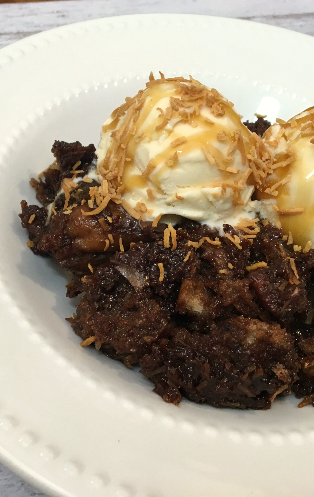 white bowl with up close shot of German Chocolate Bread Pudding with vanilla ice cream