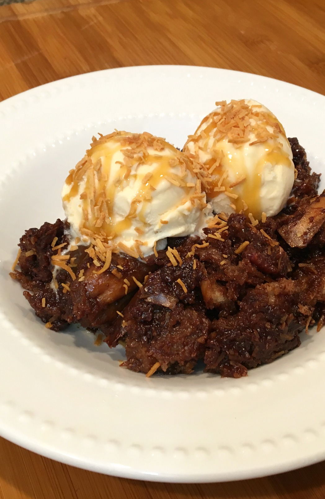 white bowl with german chocolate bread pudding, two scoops of vanilla ice cream and drizzled with caramel sauce and toasted coconut