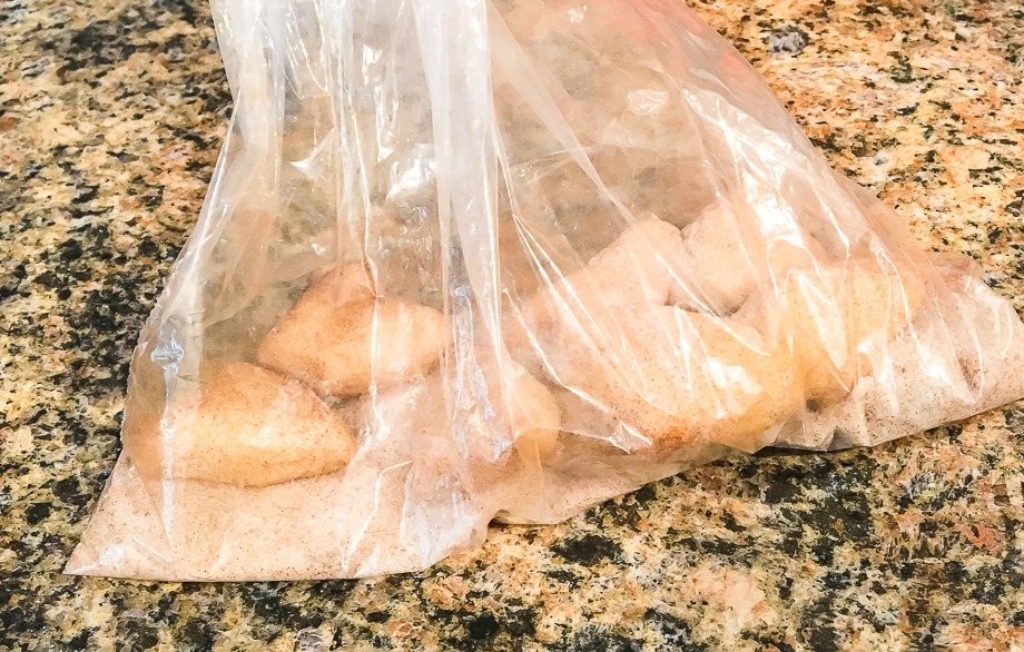 a bag filled with cinnamon sugar and pieces of biscuits