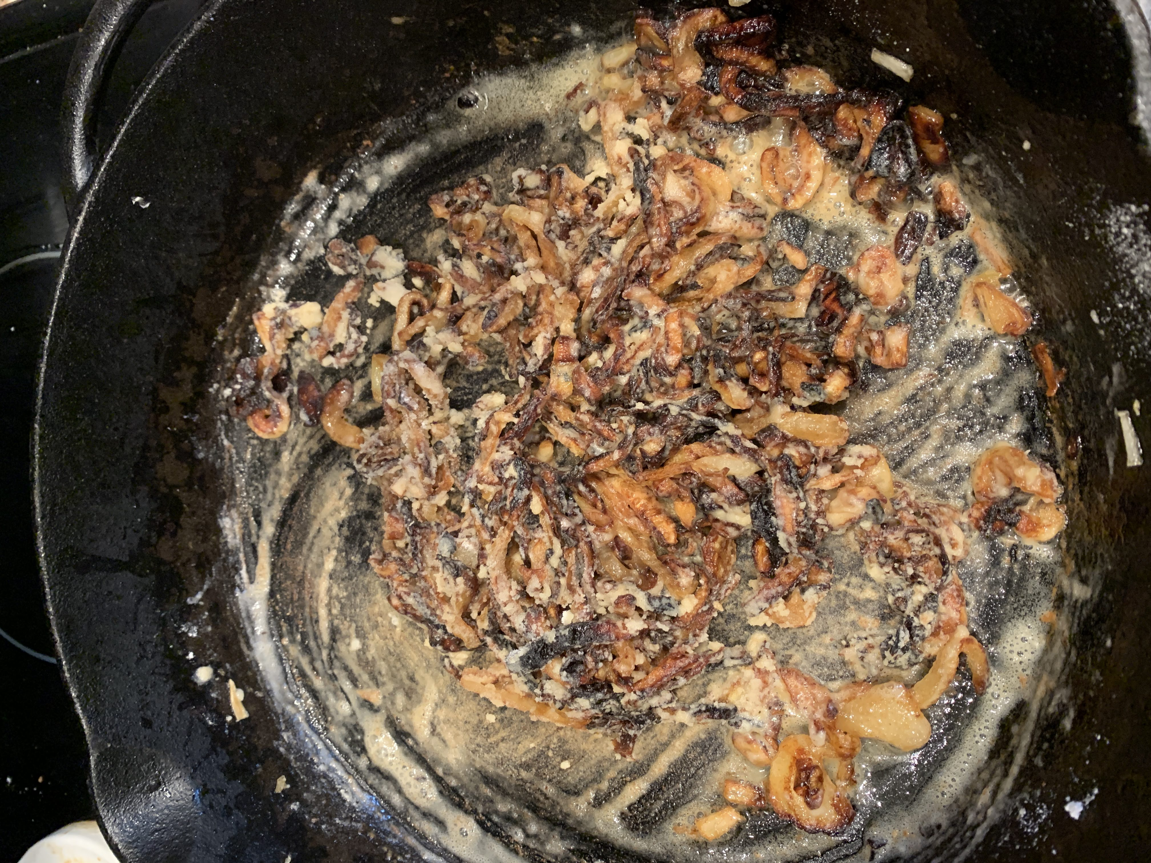 cast iron skillet with fried onions and flour mixed into a slurry