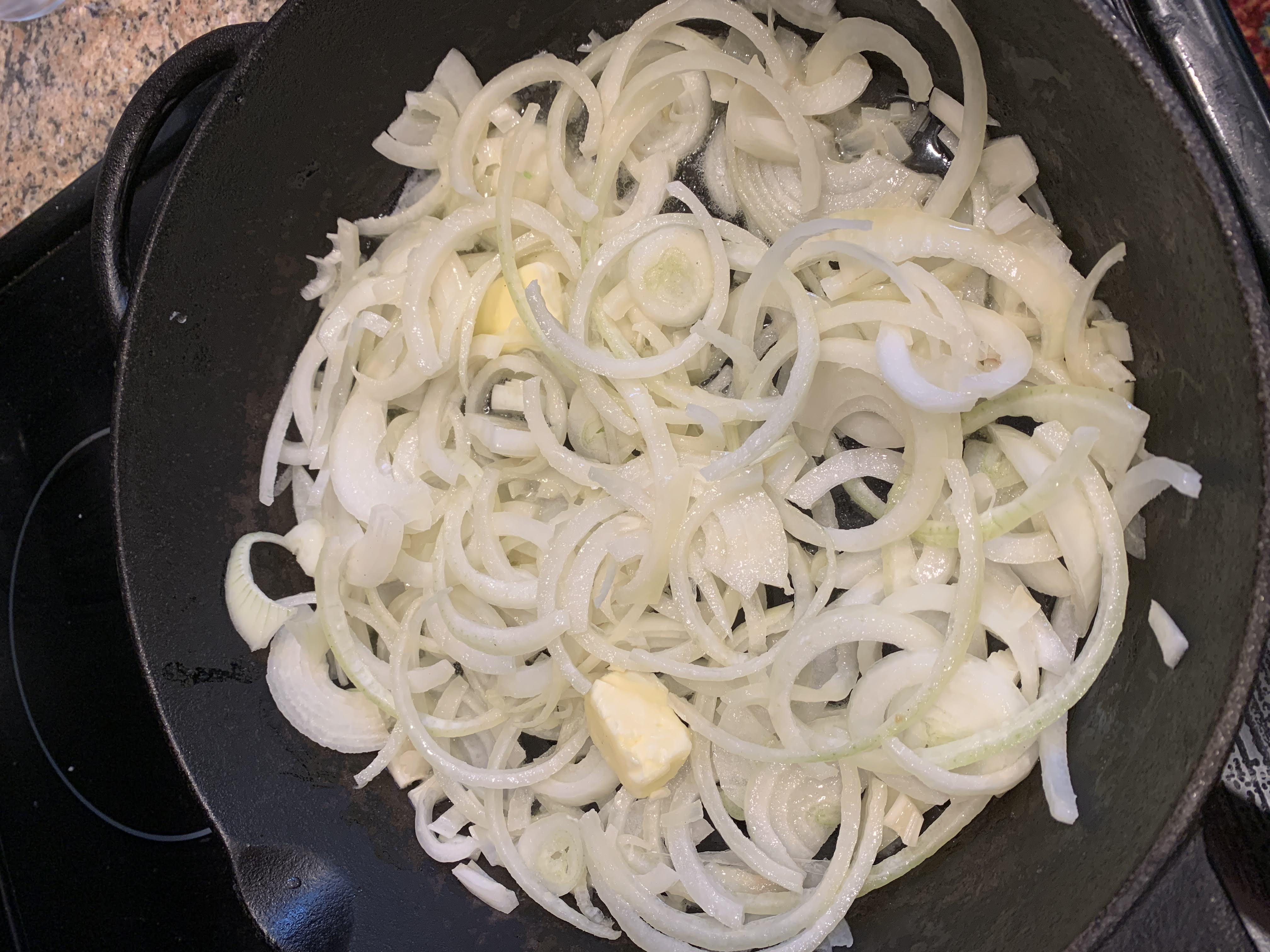 cast iron skillet with sliced onions and pats of butter