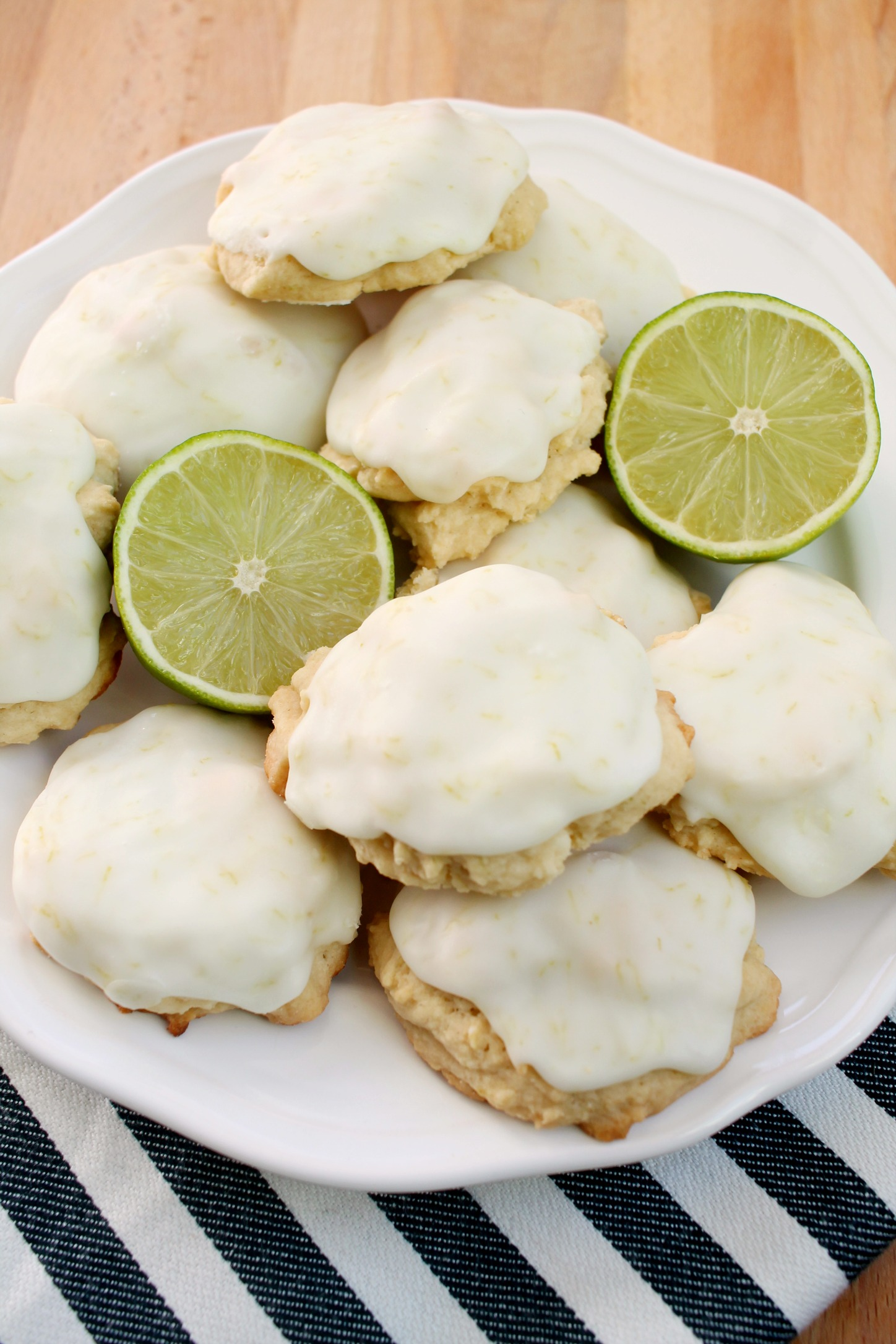 a pile of frosted lime cookies and two lime slices on a white plate with a navy and white striped towel underneath