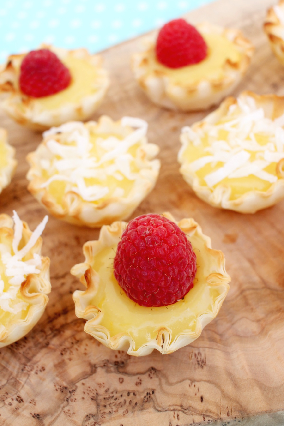 cutting board with lemon curd filled mini tart shells topped with raspberries and shredded coconut