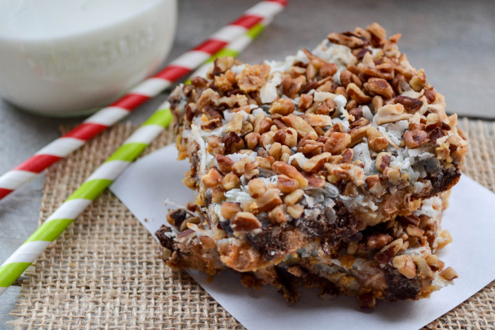 a piece of magic cookie bars on a napkin with two striped straws in the background