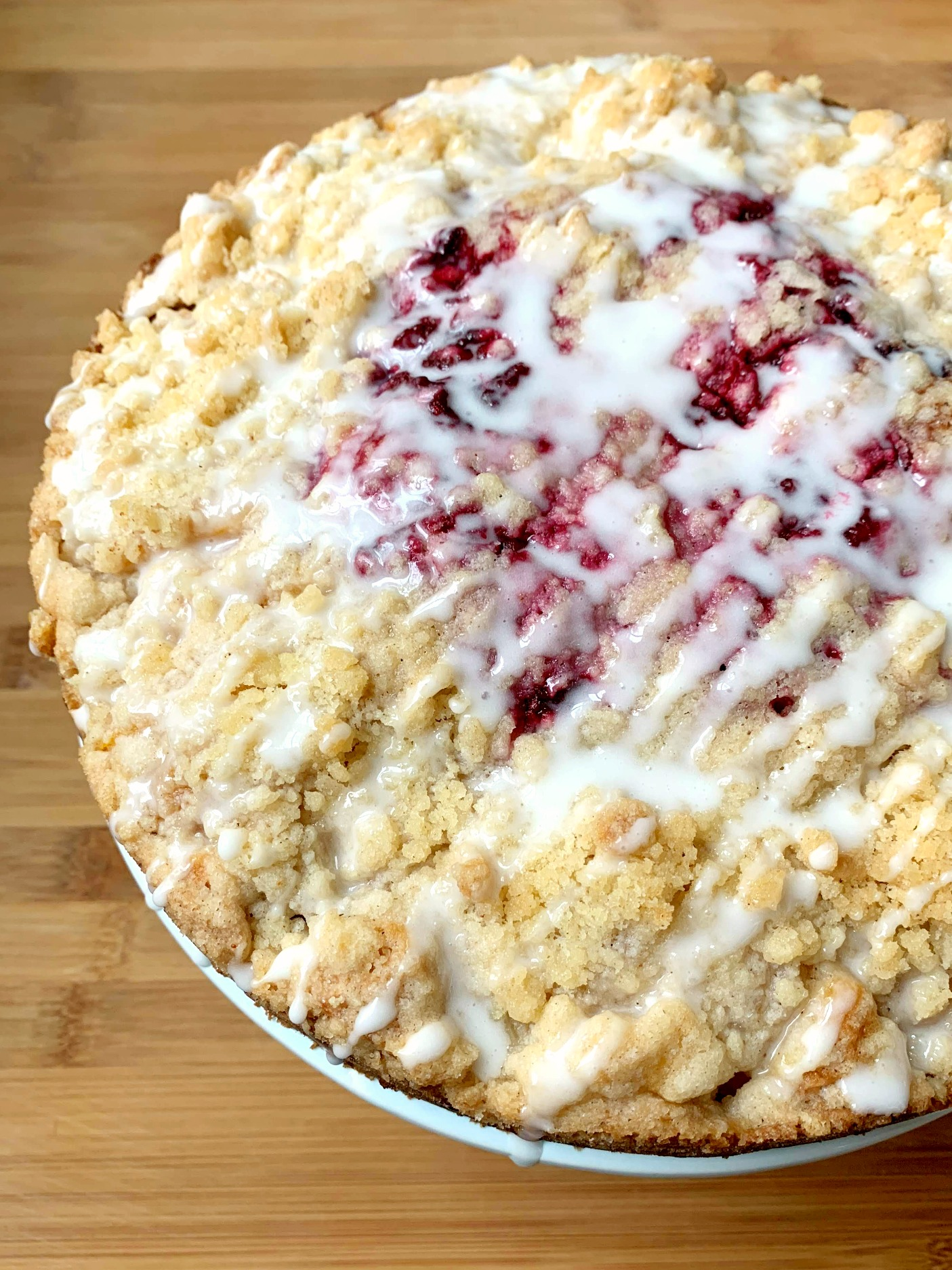 round coffee cake with crumb topping, raspberries in the center and a powdered sugar glaze