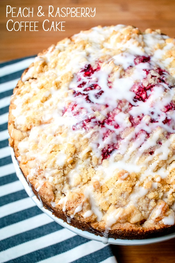 a peach raspberry round coffee cake with a crumb topping and powdered sugar glaze