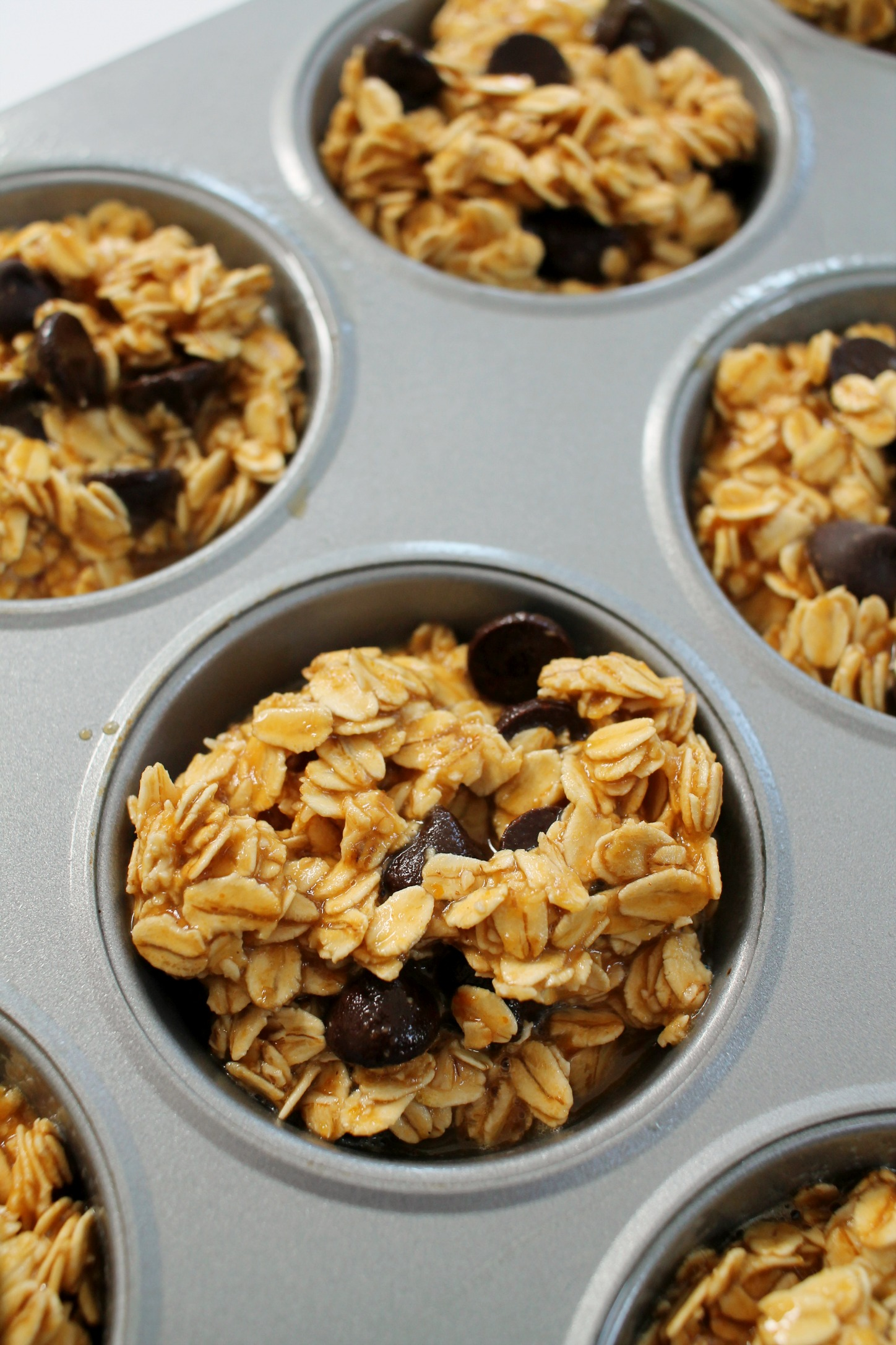 up close shot of peanut butter chocolate chip baked oatmeal muffins in the muffin pan before baking