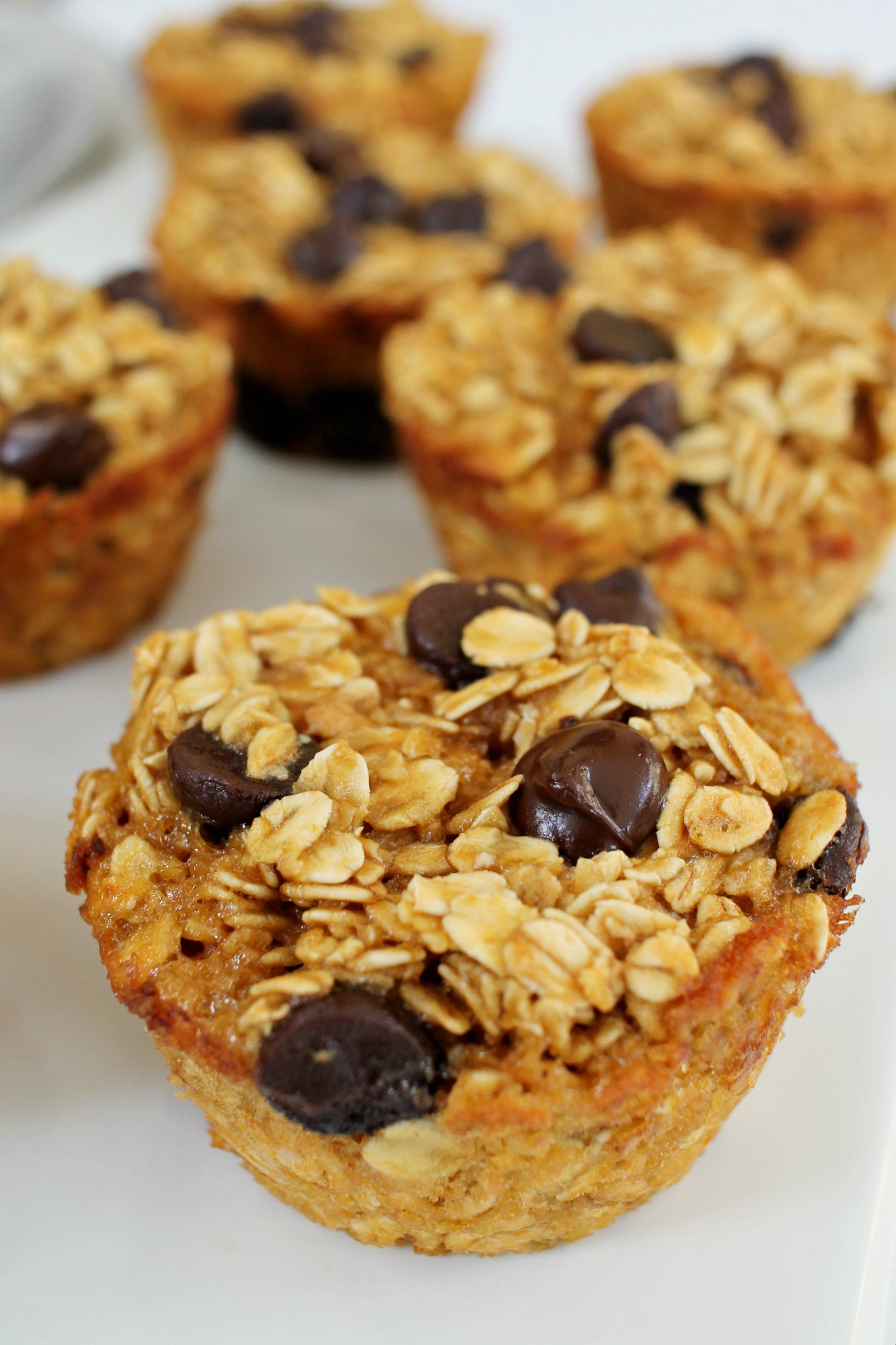 up close shot of peanut butter chocolate chip baked oatmeal muffin with more in the background