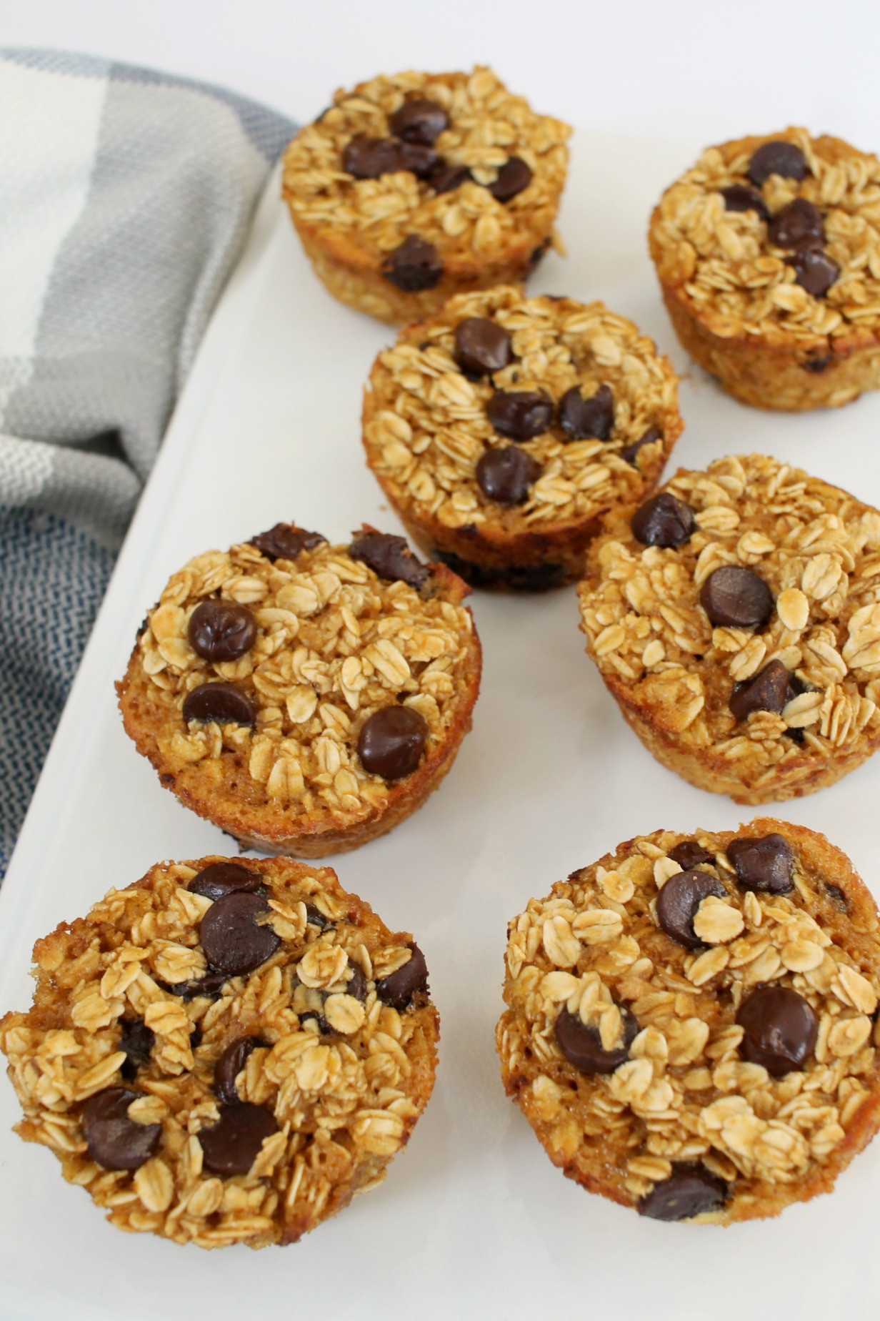 white rectangle plate with 7 peanut butter chocolate chip baked oatmeal muffins