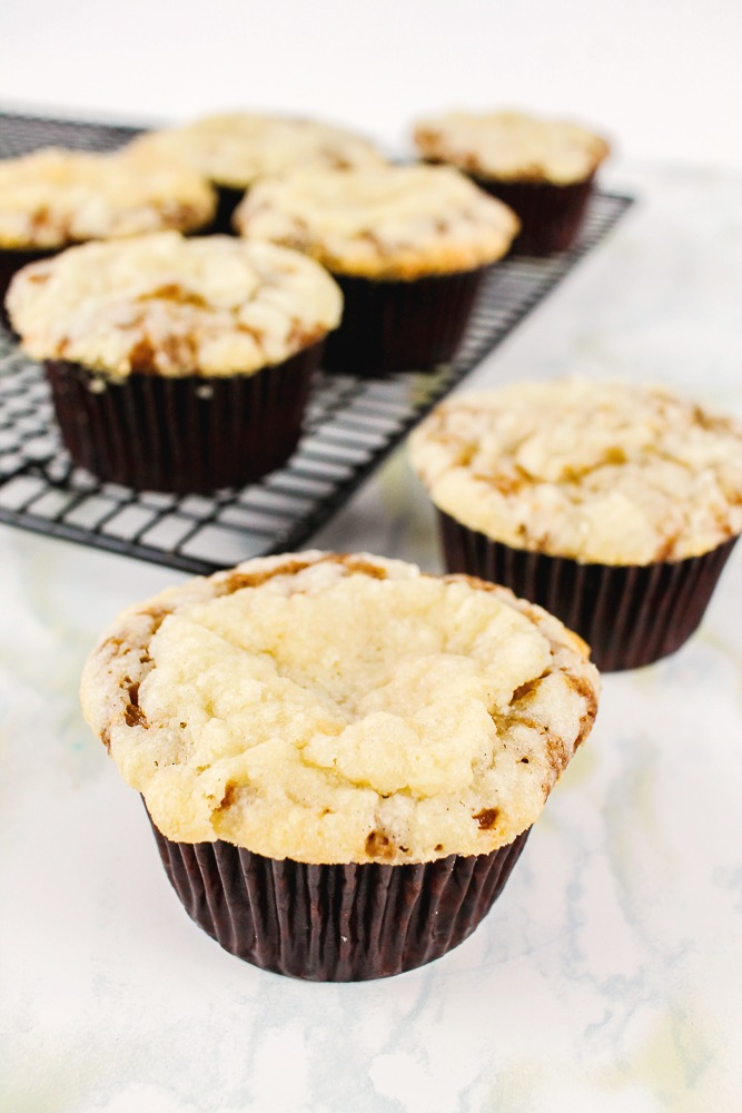 pear muffin with crumb topping in front of a cooling rack with more muffins