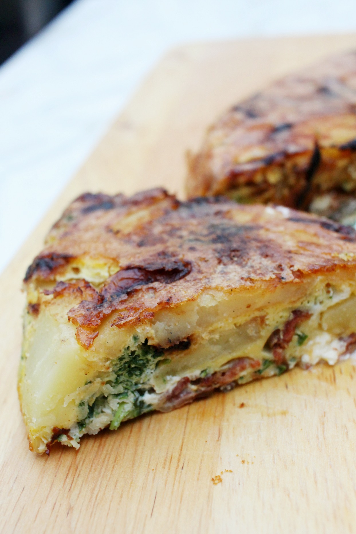 a slice of a potato and bacon frittata on a wooden cutting board