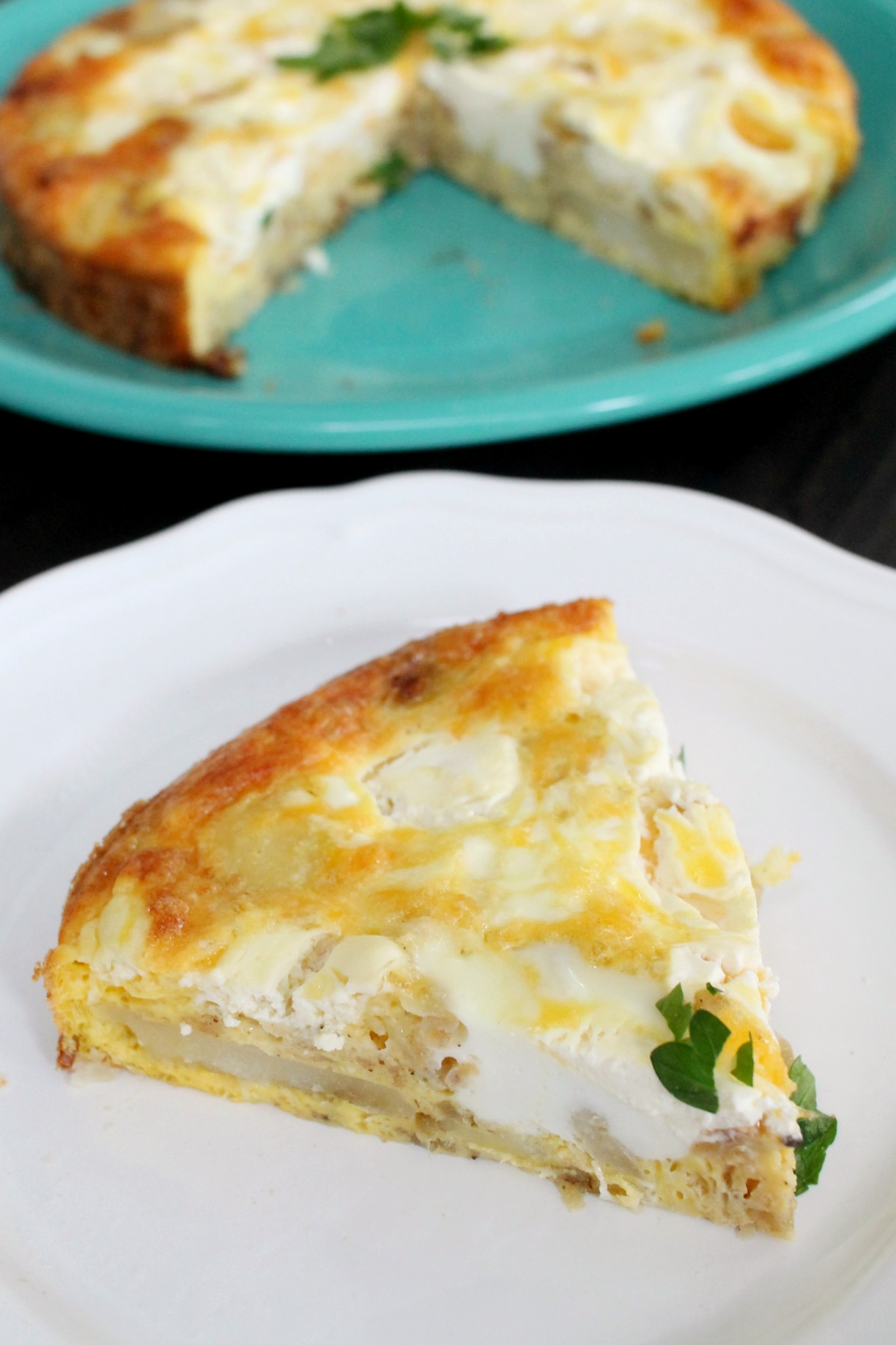 a slice of frittata on a white plate with the rest in the background