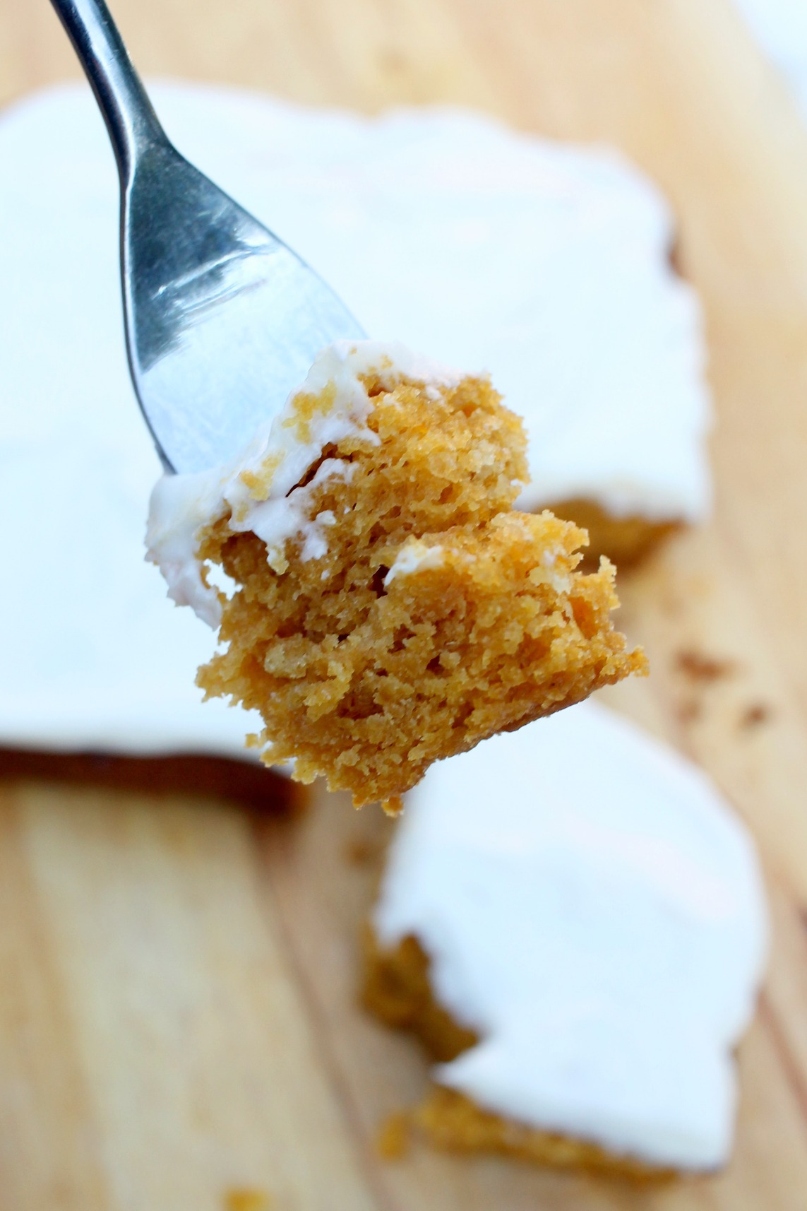a fork holding a bite of pumpkin cake with the rest of the cake in the background