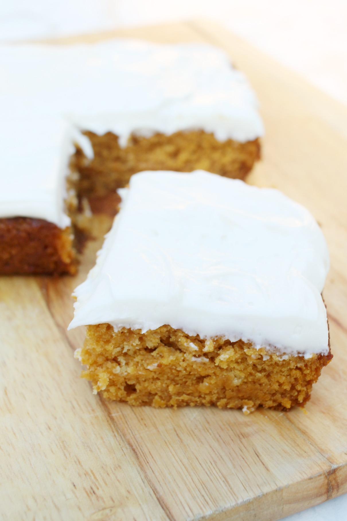 a slab of Pumpkin Cake with Cream Cheese Frosting with the corner piece cut out and pushed to the front of the picture