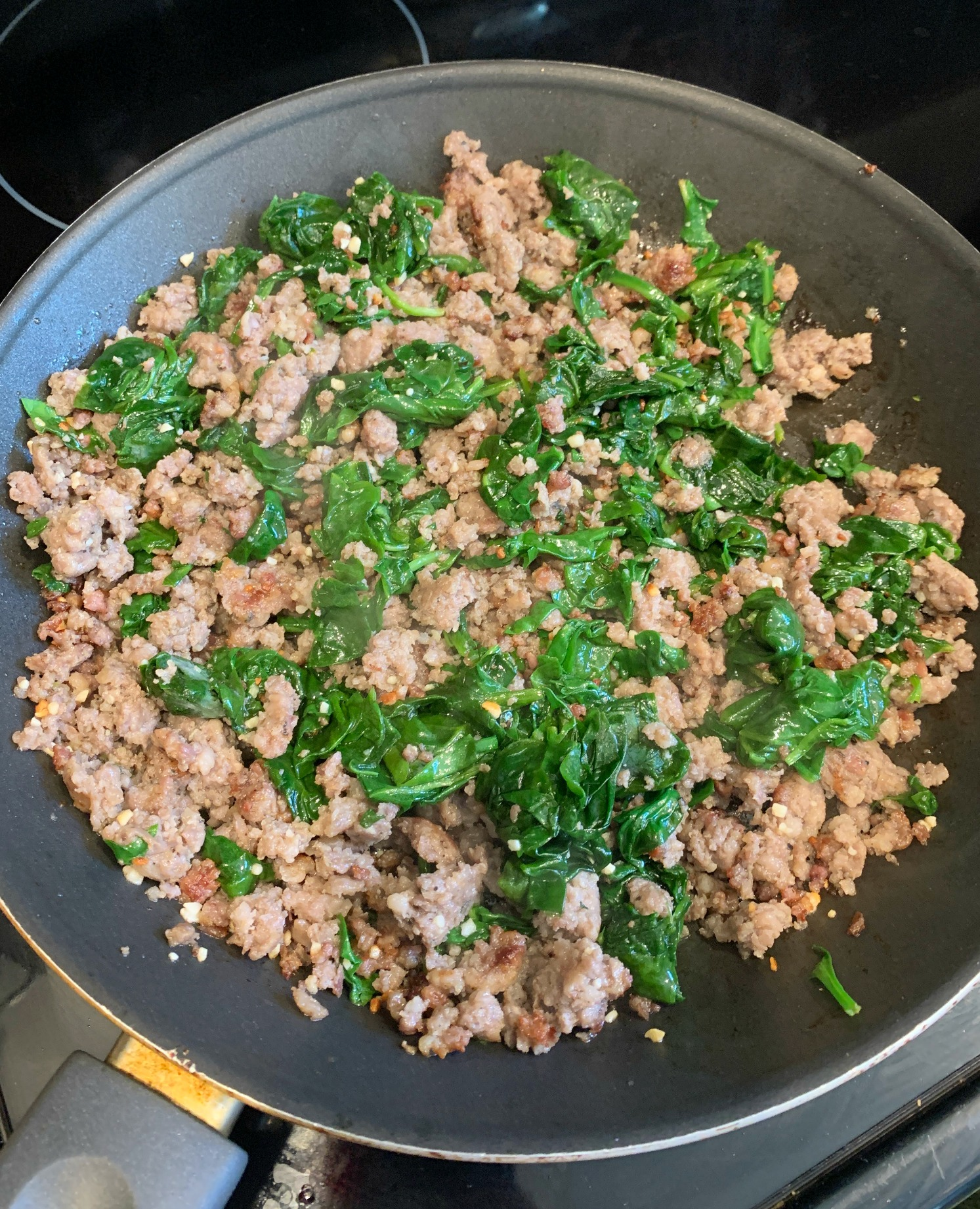 frying pan with cooked ground sausage and wilted spinach