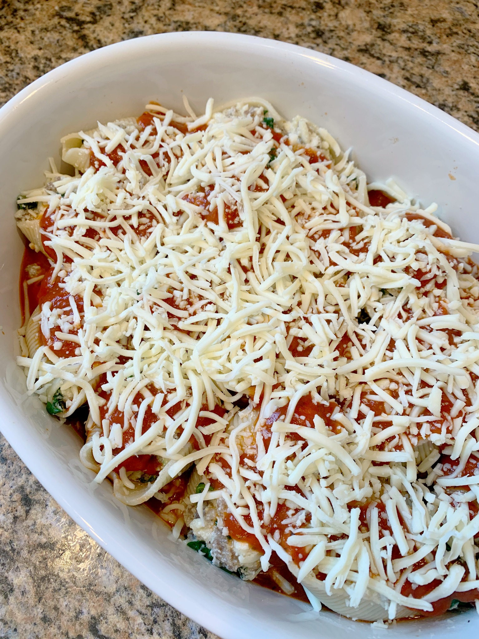stuffed shells topped with grated cheese before baking
